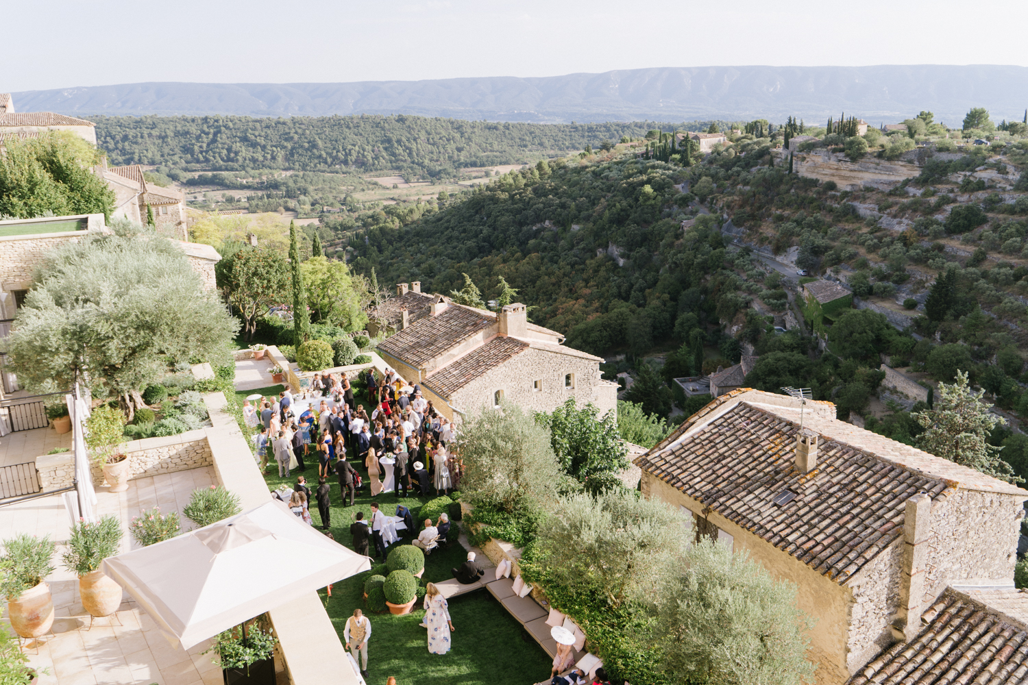 Guests mingle at a chateau in Gordes, France after the wedding ceremony; Sylvie Gil Photography