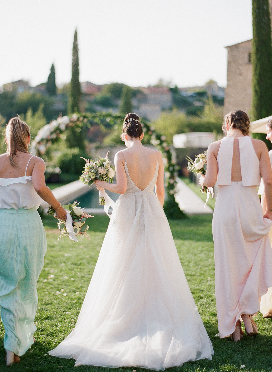 Bride and bridesmaids walk together near the chateau in Gordes, France; Sylvie Gil Photography