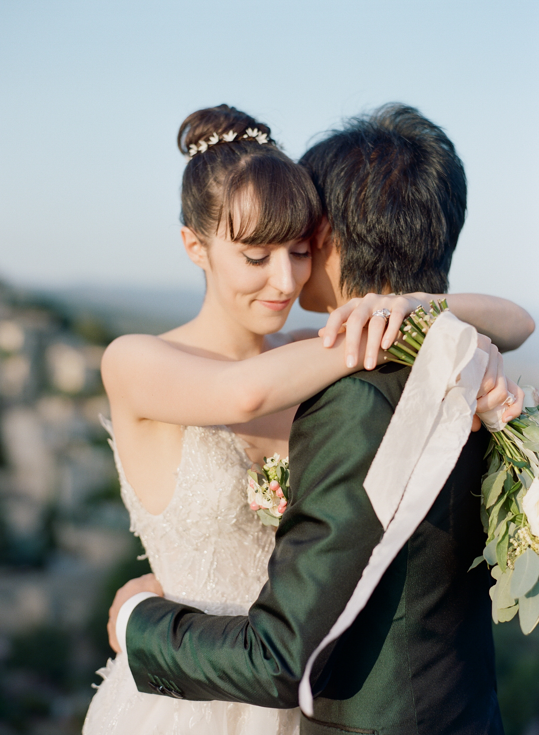 Bride and groom embrace on a hill above the village of Gordes, France; Sylvie Gil Photography