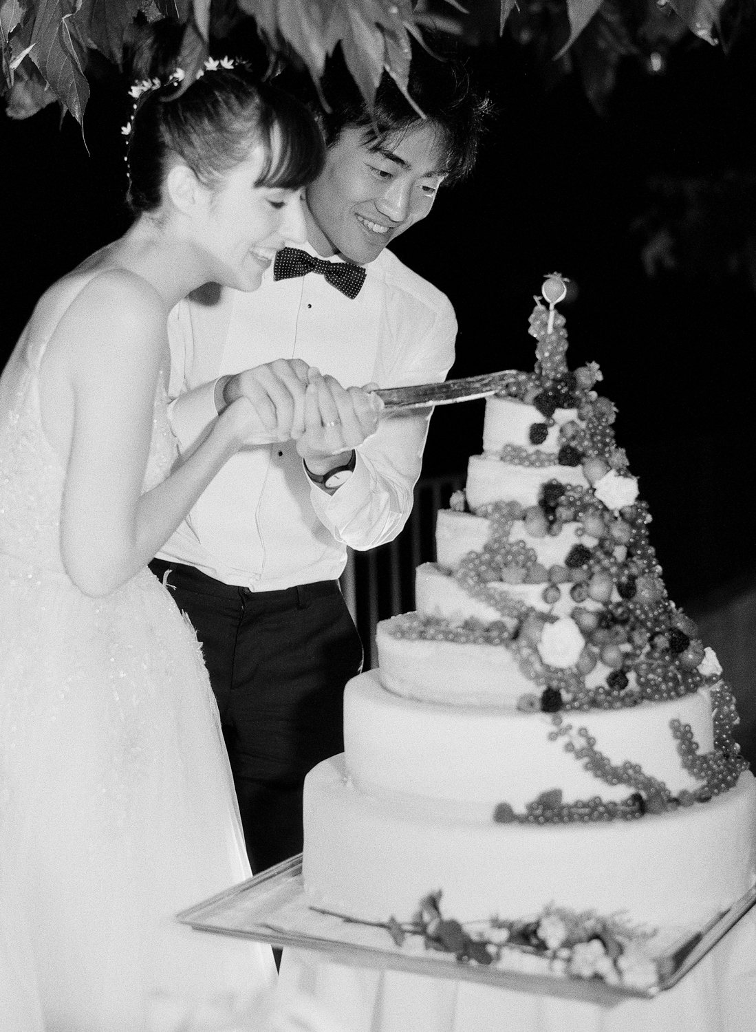 """Bride and groom cut their wedding """"cake"""" comprised of wheels of cheese; Sylvie Gil Photography"""