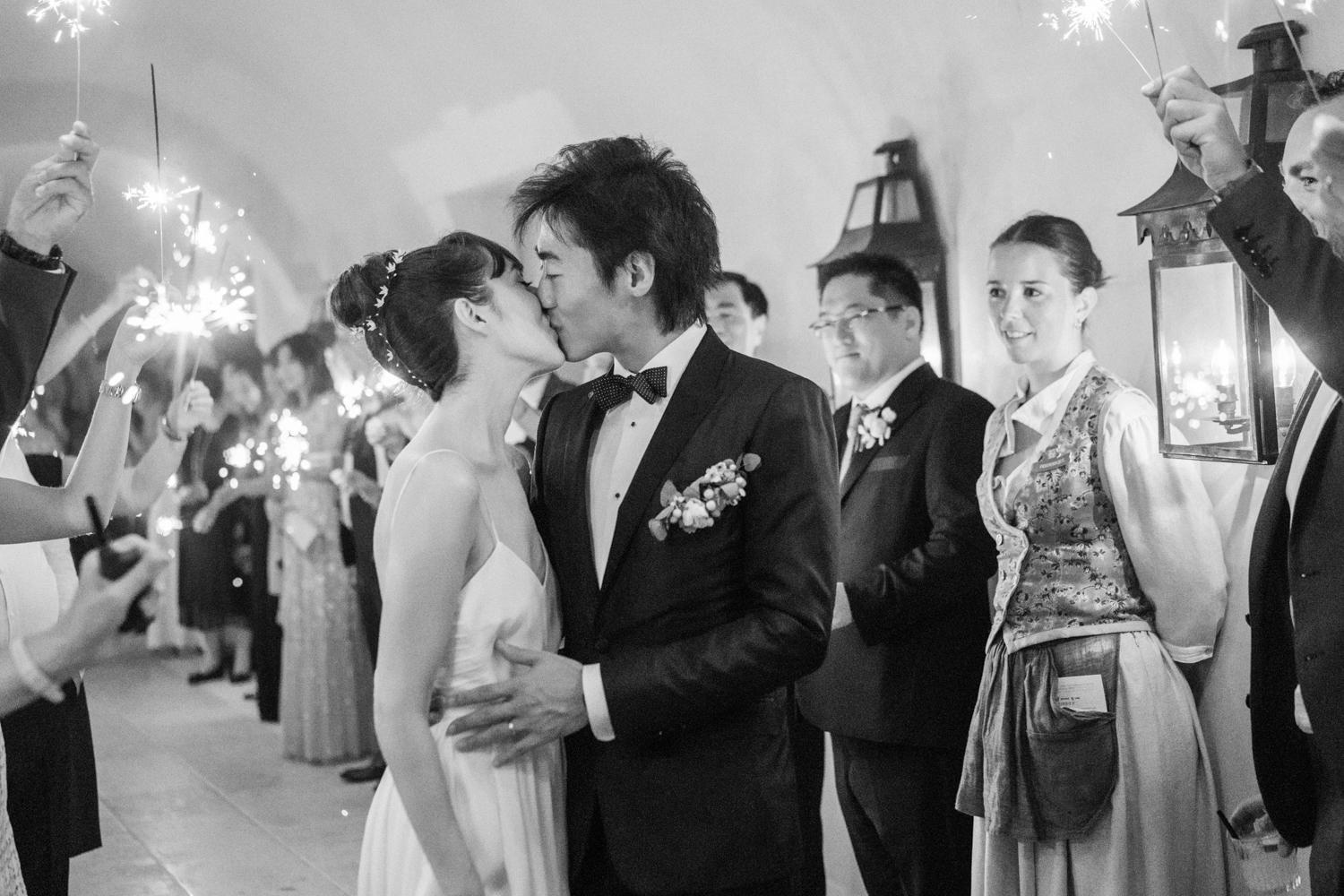 The bride and groom kiss among their friends and families holding sparklers to send them off; Sylvie Gil Photography