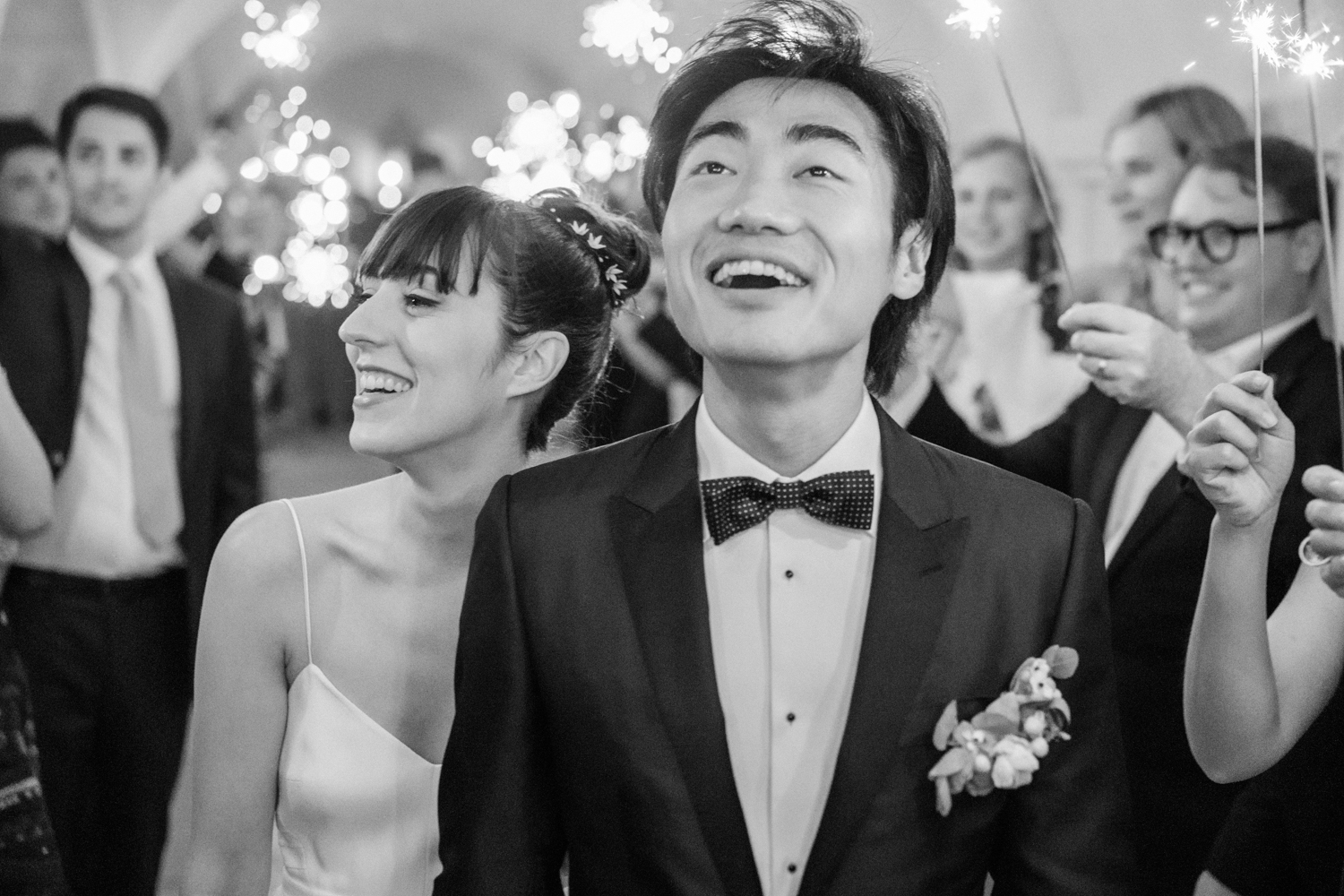 Bride and groom walk through their friends and family holding sparklers at the end of the night; Sylvie Gil Photography