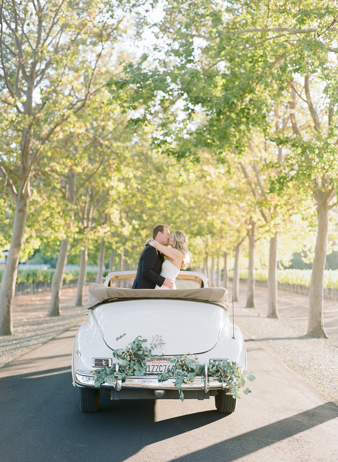 Bride and groom kiss in a vintage convertible, decorated with eucalyptus branches; Sylvie Gil Photography