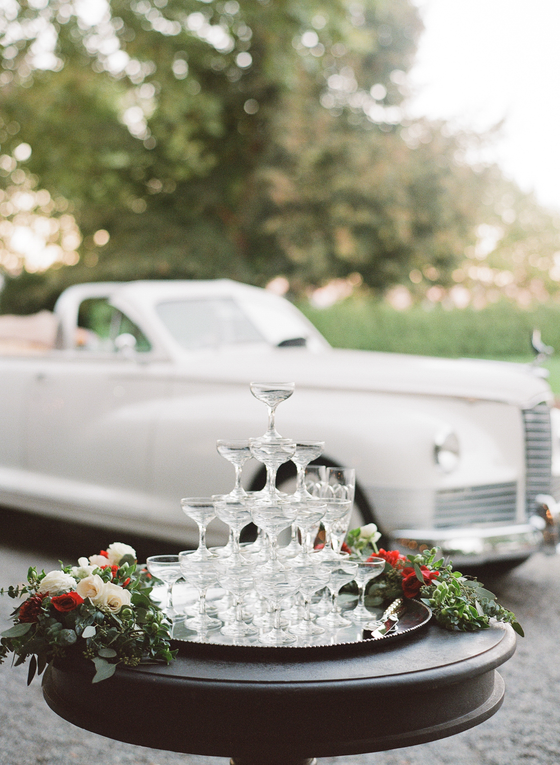 A champagne tower displayed in front of the vintage convertible getaway car at a Beaulieu Gardens wedding; Sylvie Gil Photography