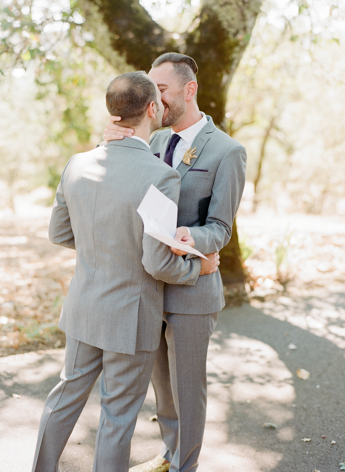 Grooms share a kiss during their first look at Kunde Winery; Sylvie Gil Photography