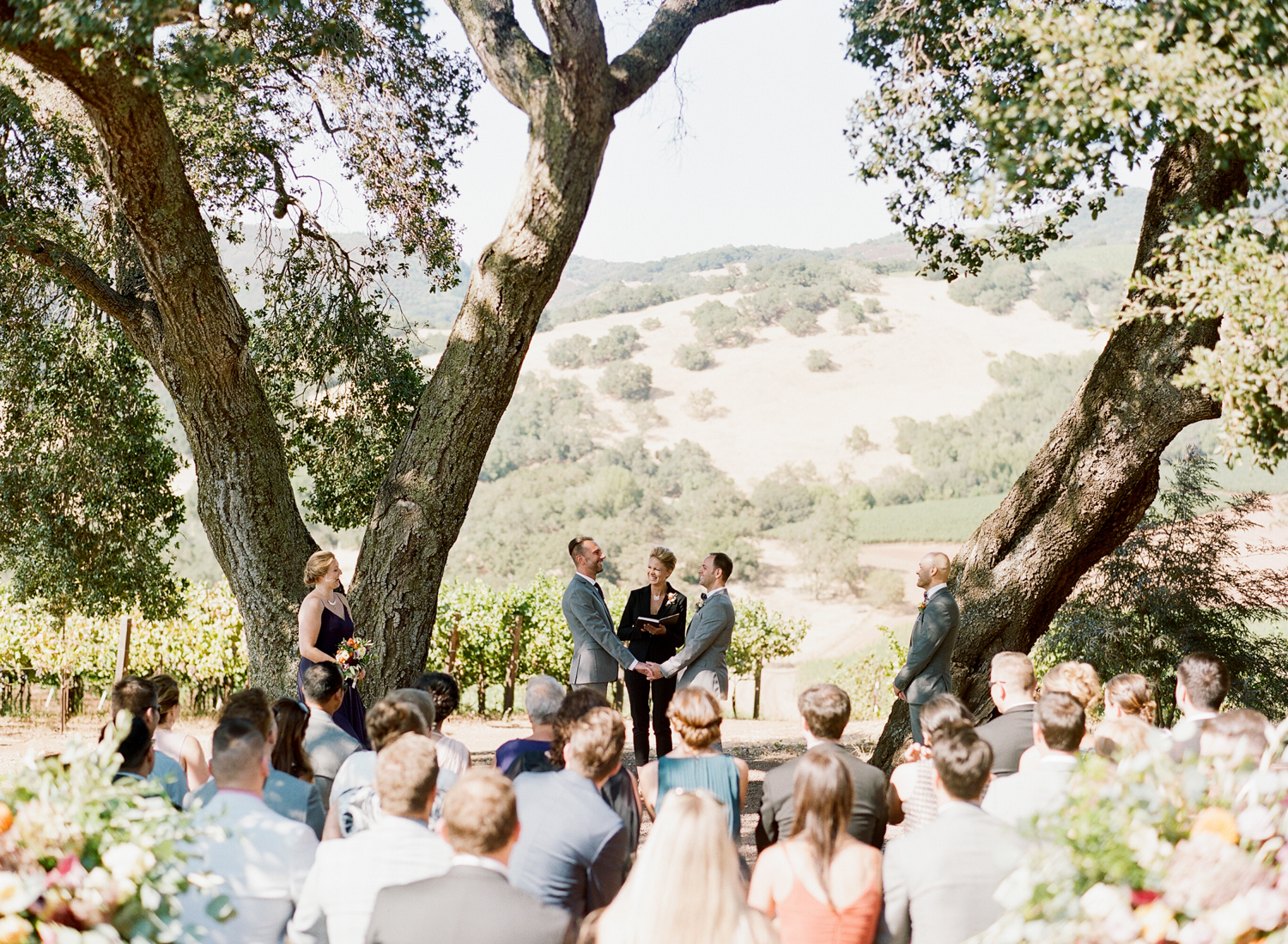 Grooms share vows during their wedding ceremony at Kunde Winery in Napa Valley; Sylvie Gil Photography