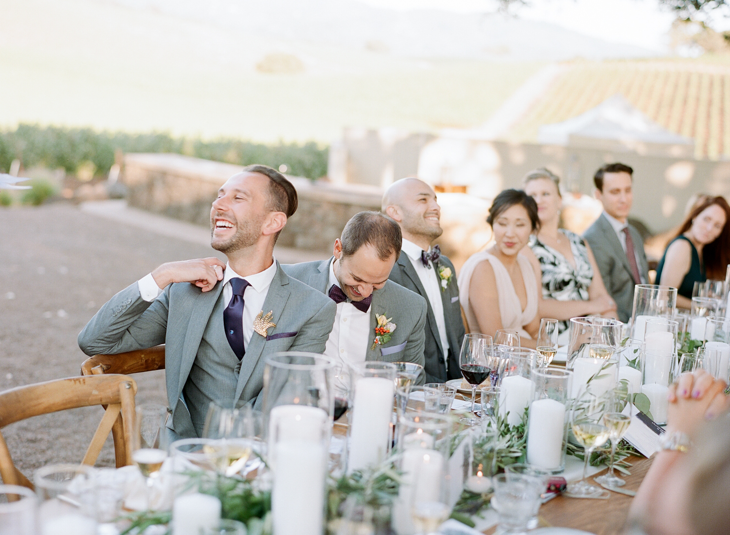 Guests and grooms laugh during toasts at Kunde Winery; Sylvie Gil Photography