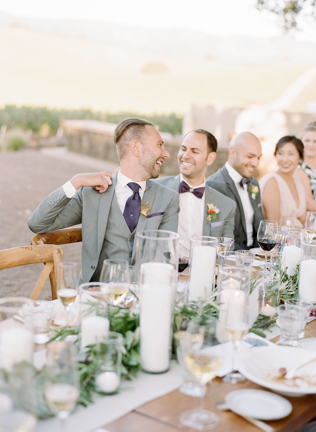 The grooms share a laugh during toasts at their Kunde Winery wedding reception; Sylvie Gil Photography