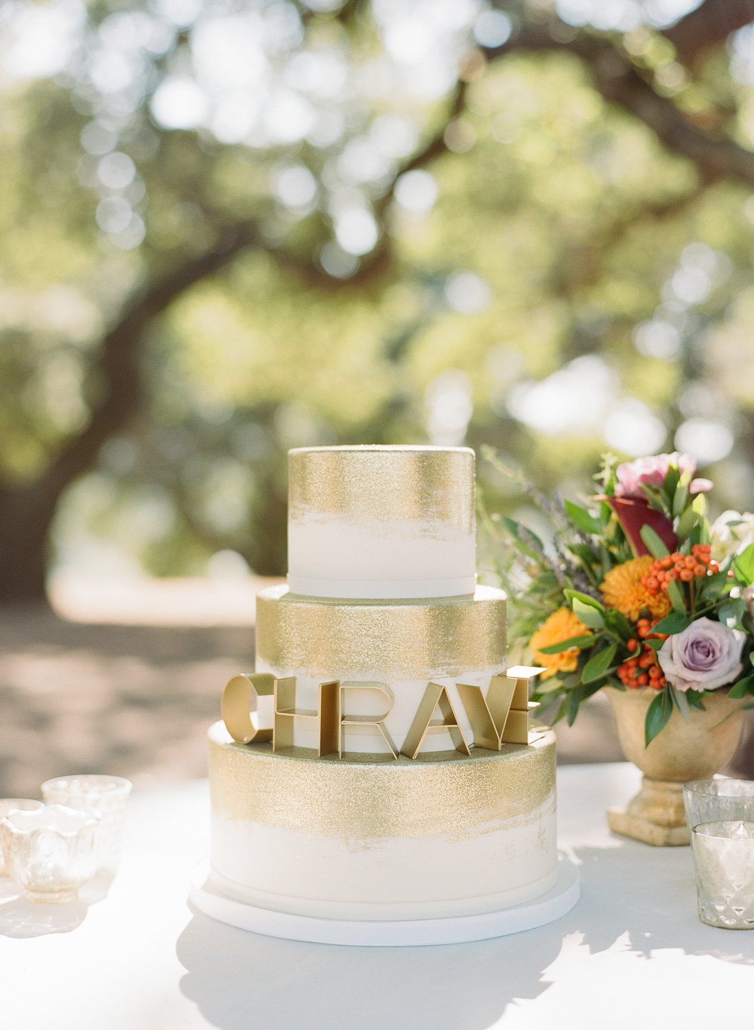 """A three-tier, gold-trimmed wedding cake with the grooms' couple name, """"CHRAVE""""; Sylvie Gil Photography"""