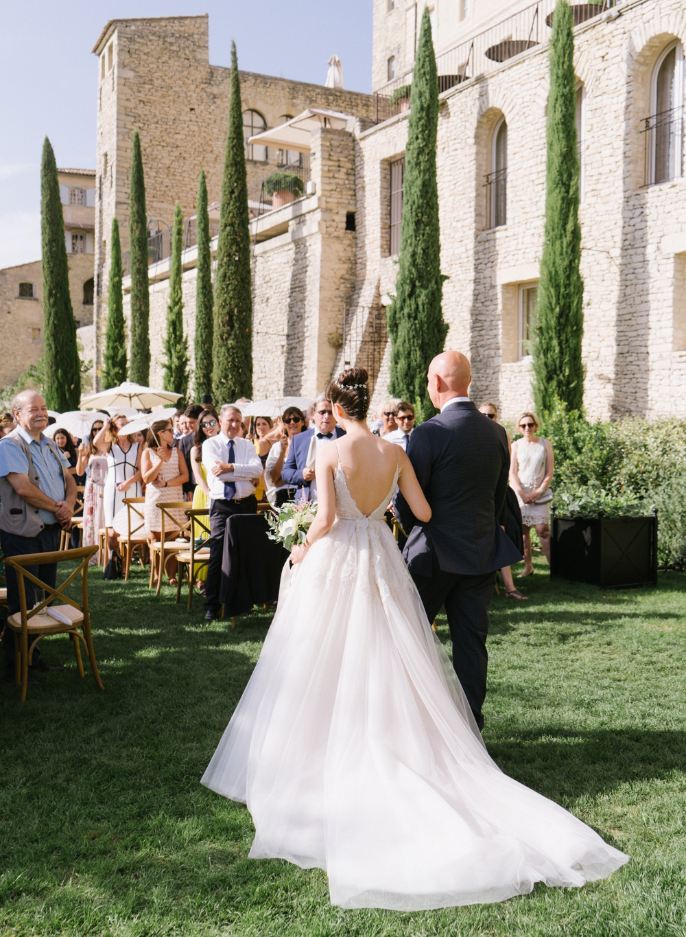 The bride and her father walk down the aisle at the ceremony in Gordes, France; Sylvie Gil Photography