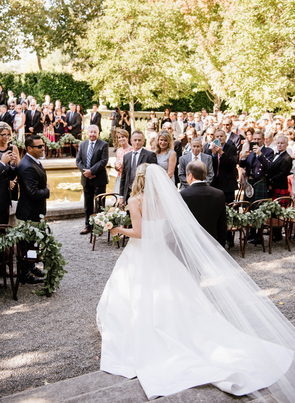The bride and her father walk toward the ceremony arbor at Beaulieu Gardens; Sylvie Gil Photography
