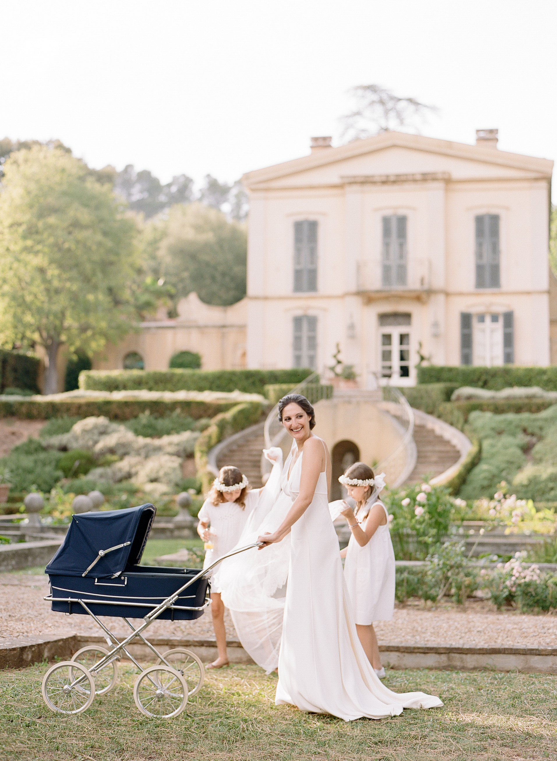 The bride pushes her baby in a pram with the flower girls; Sylvie Gil Photography