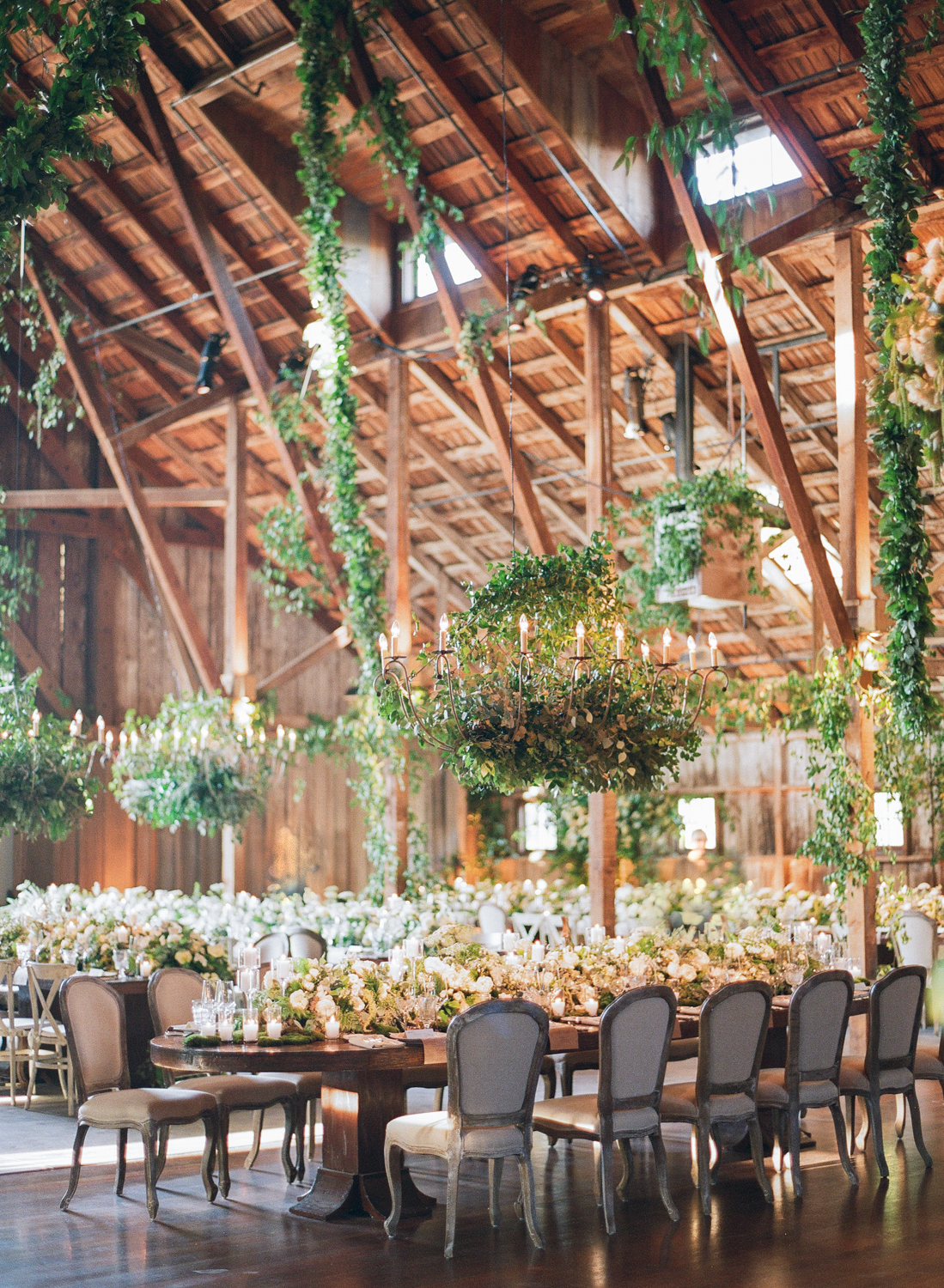 Leafy arrangements hung from the beams in the reception barn at Santa Lucia Preserve; Sylvie Gil Photography