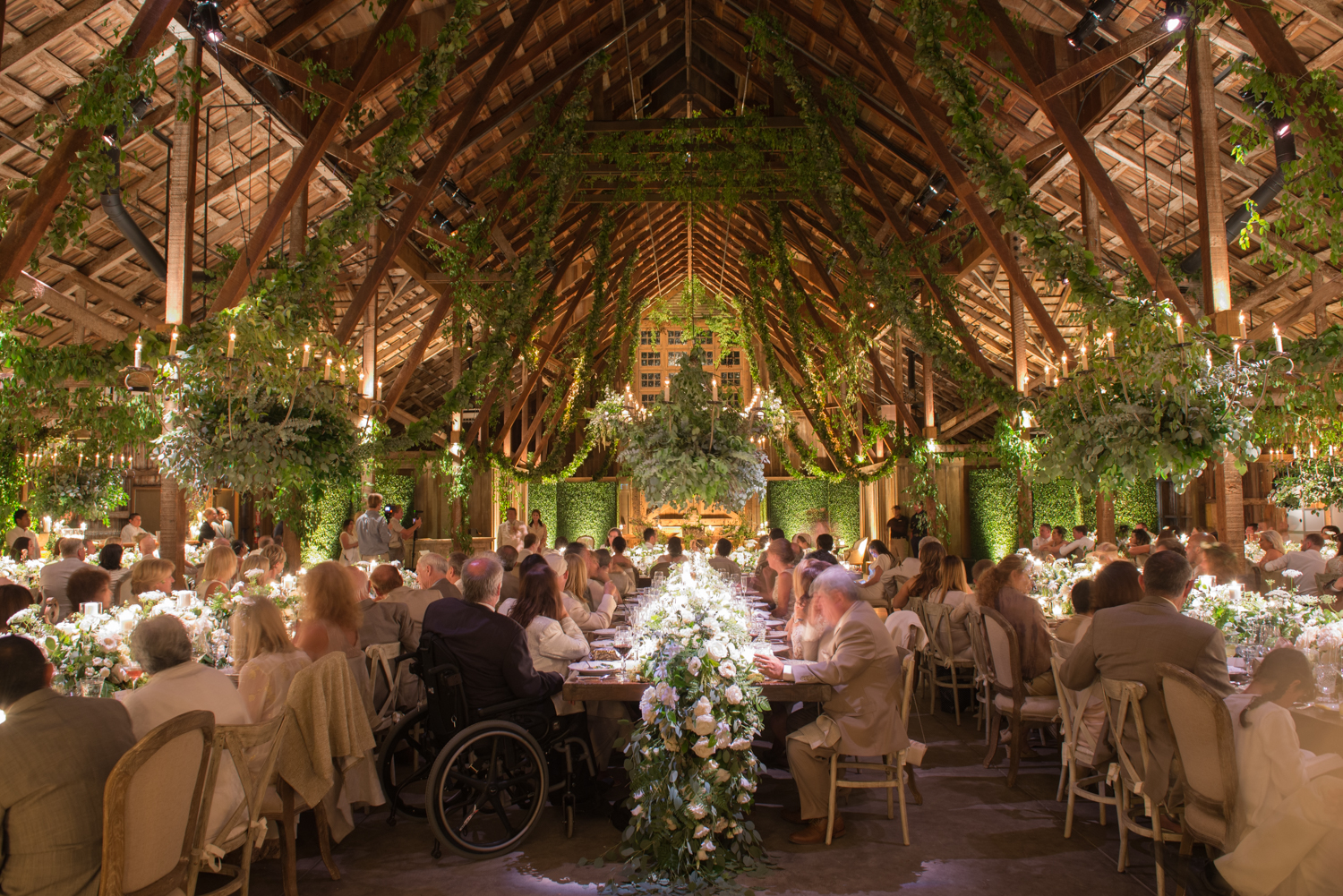 A wedding reception in the forest-decorated barn at Santa Lucia Preserve; Sylvie Gil Photography