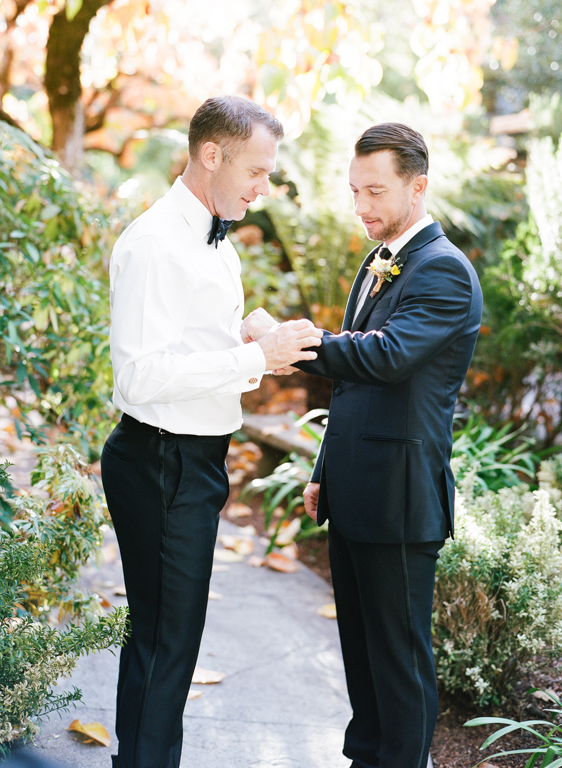 Grooms putting on their cufflinks before their wedding ceremony in St. Helena, California; Sylvie Gil Photography