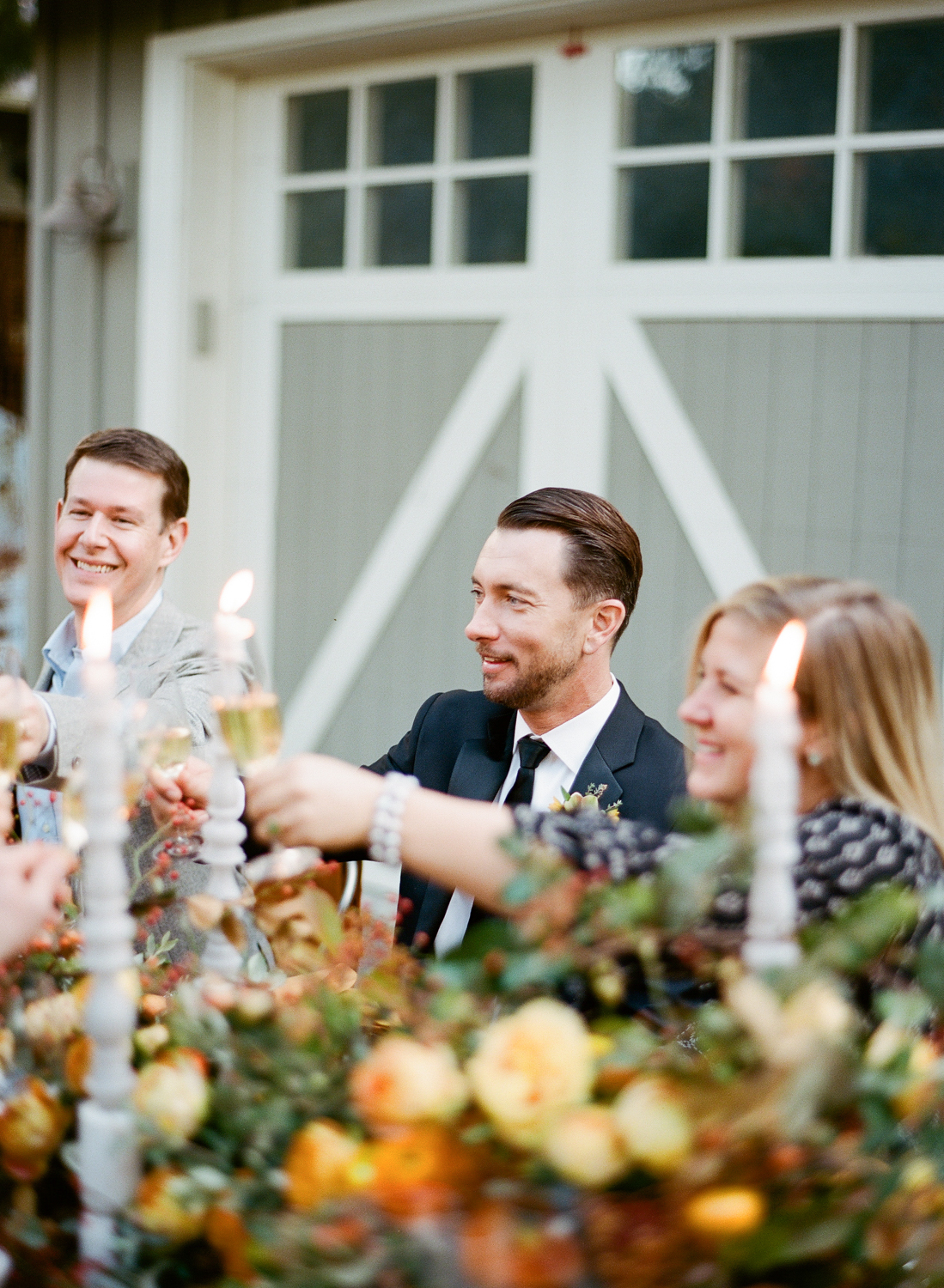 Grooms toast champagne with wedding guests at their outdoor reception in St. Helena, California; Sylvie Gil Photography