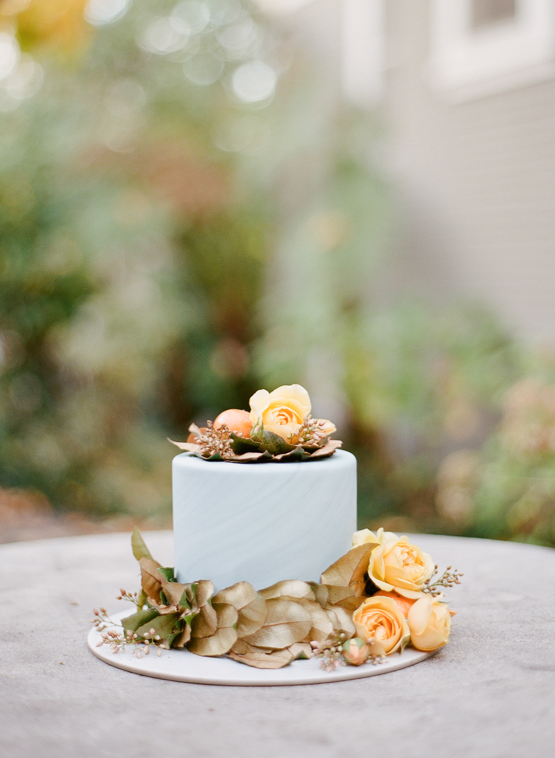 A one-tier, slate marble wedding cake decorated with orange roses and whole persimmons; Sylvie Gil Photography