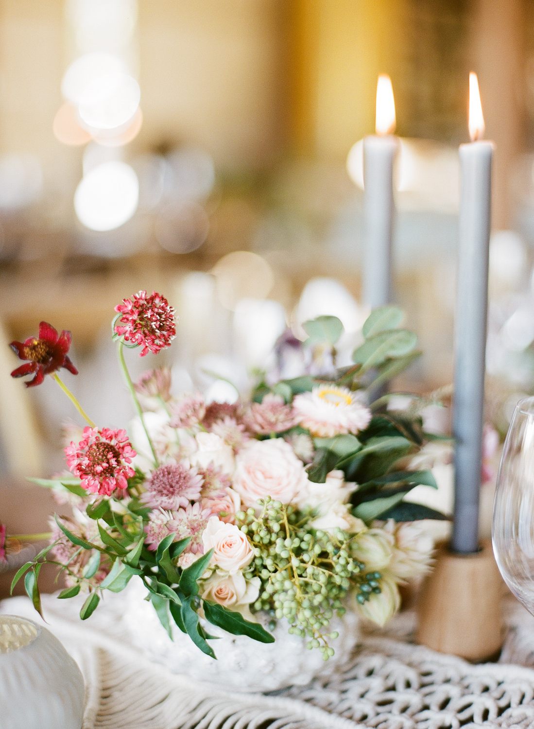Blush, burgundy, and lilac blooms on a macrame table runner at the Napa wedding reception; Sylvie Gil Photography