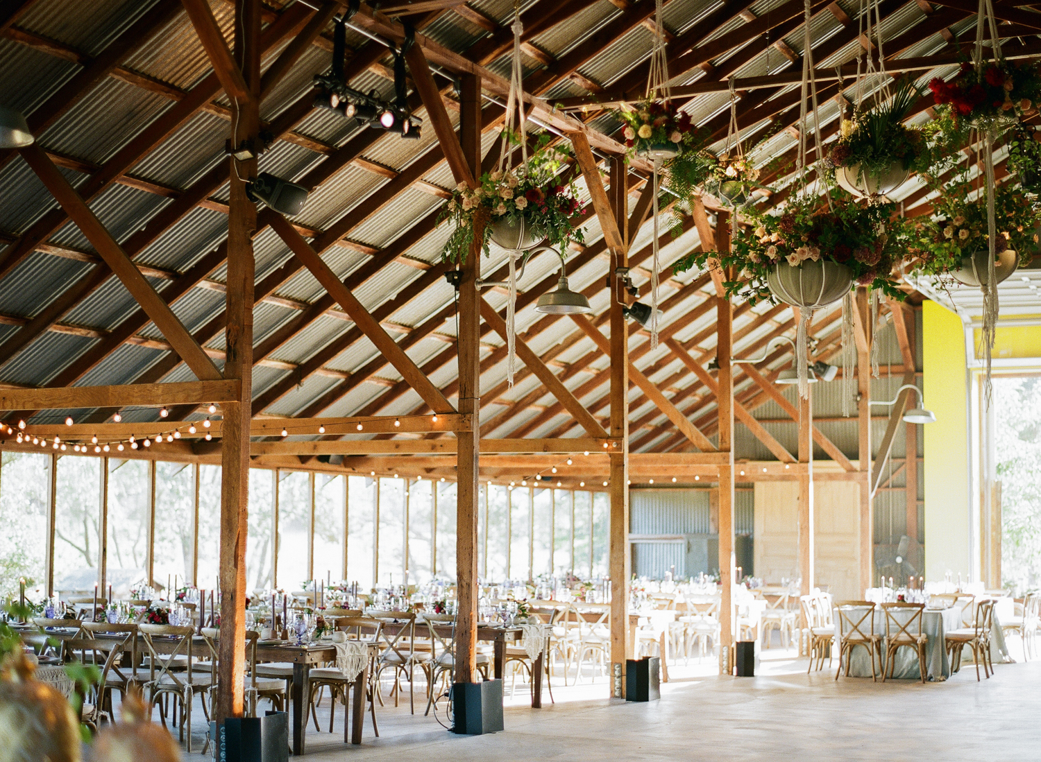 A Napa ranch wedding reception held in an airy barn with hanging planters and bohemian decor; Sylvie Gil Photography