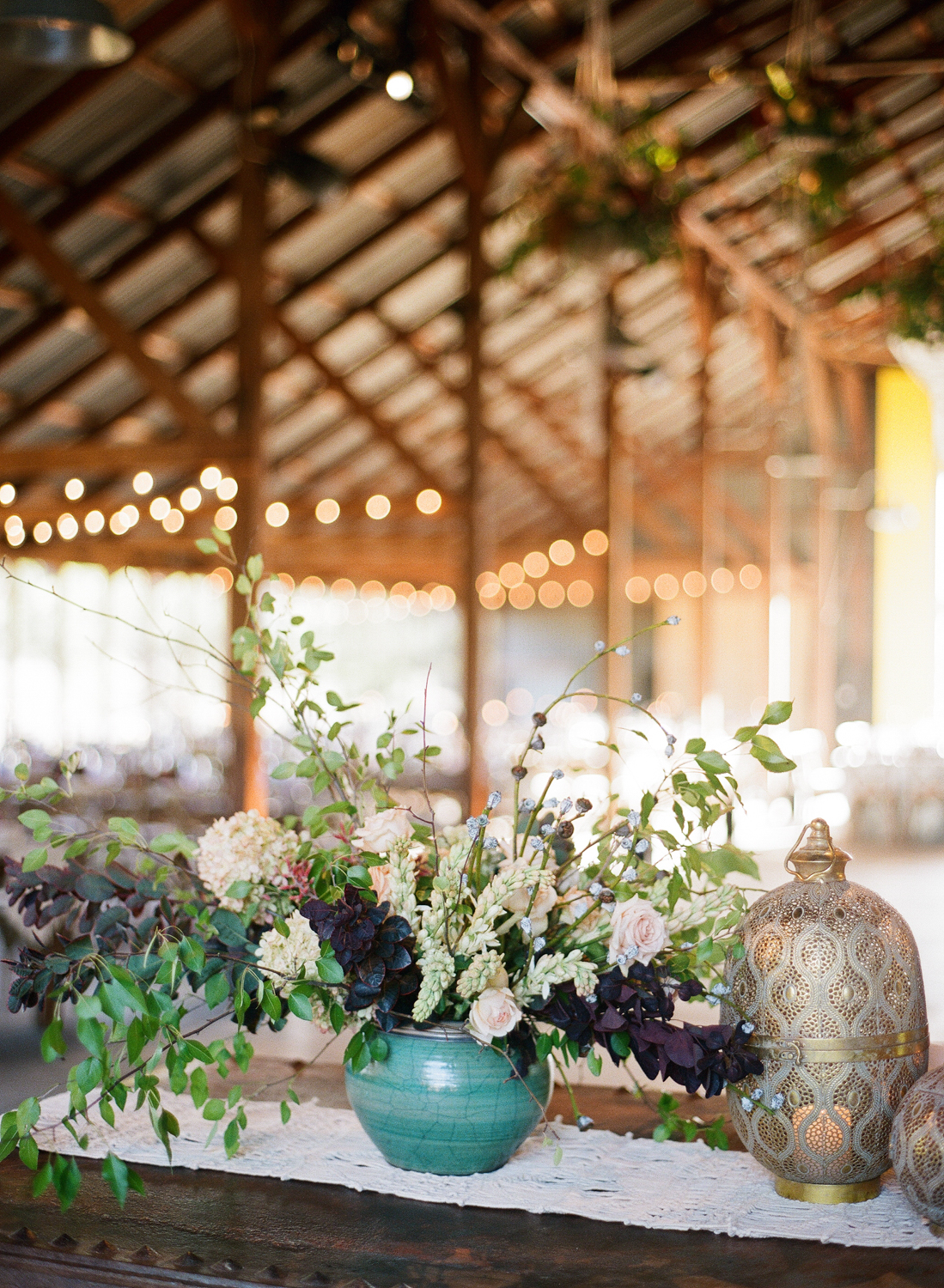 Jewel toned decor and bohemian lanterns decorate the wedding reception in an airy barn; Sylvie Gil Photography