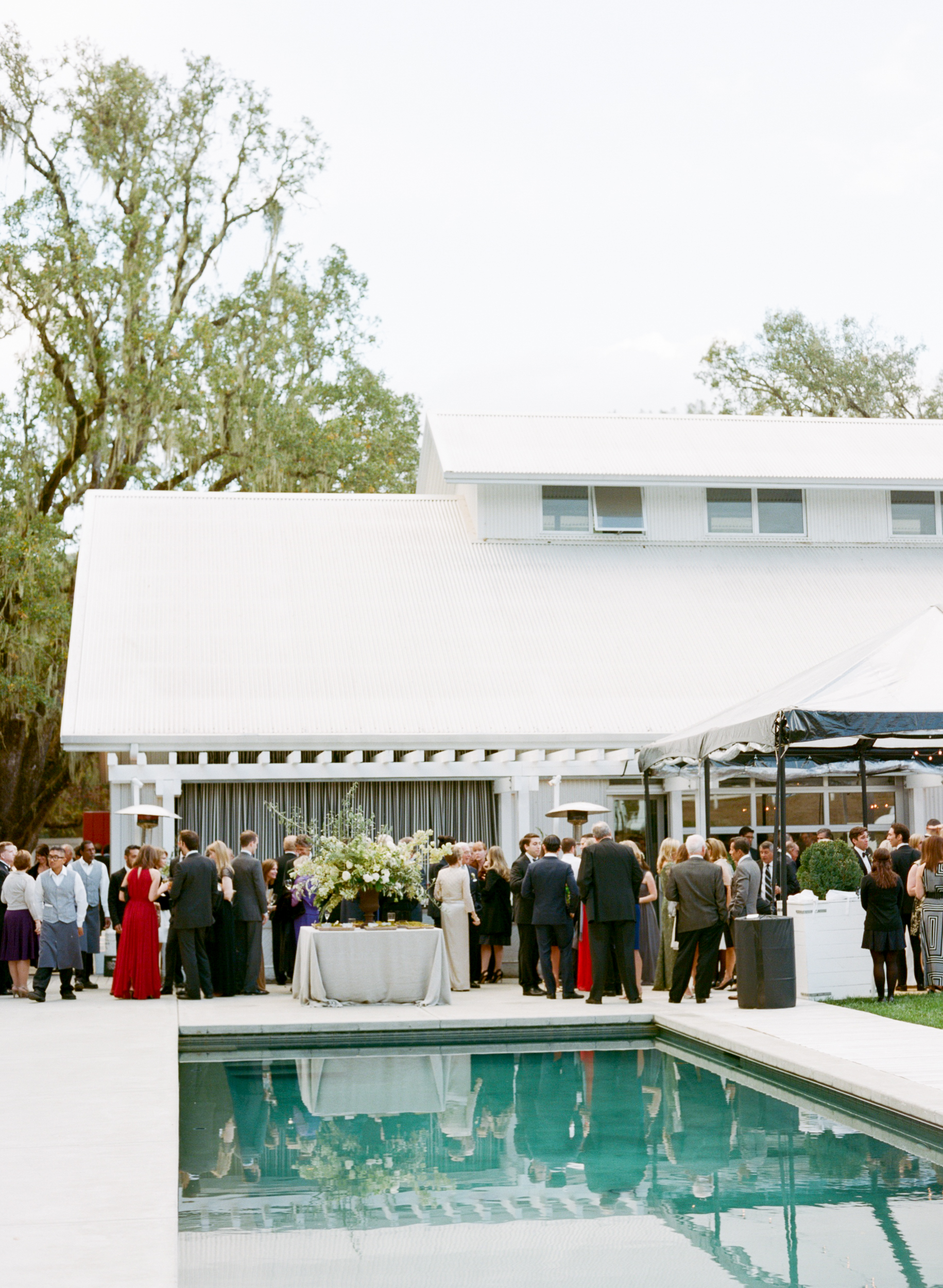 Guests mingle by the pool for wedding reception cocktails at Durham Ranch in St. Helena, California; Sylvie Gil Photography