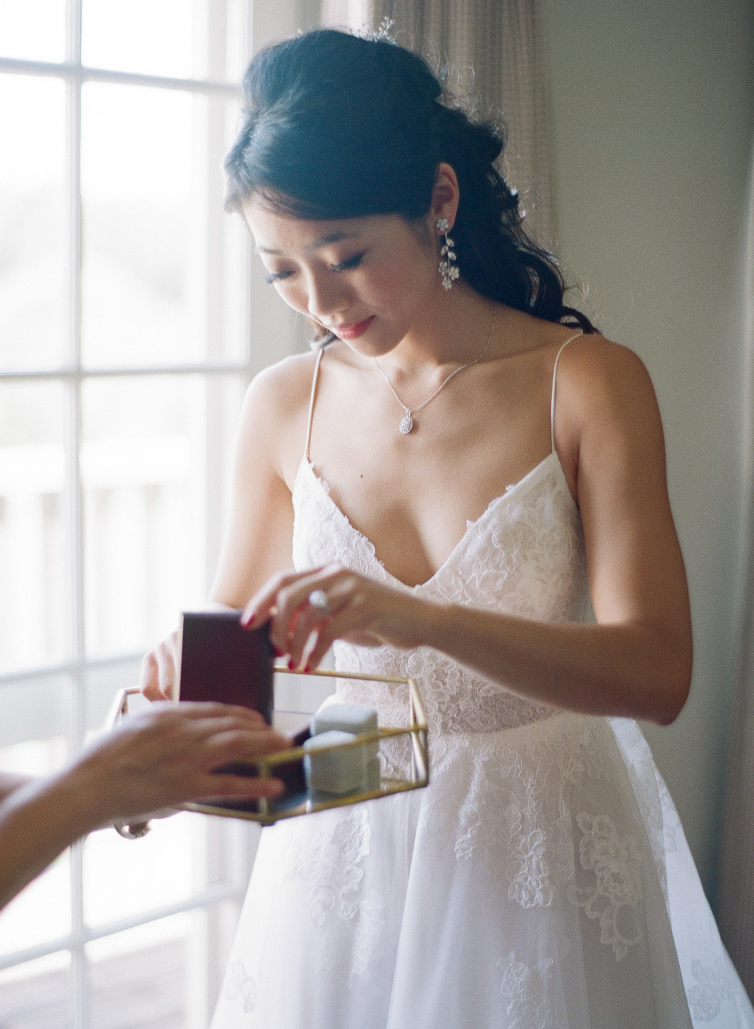 The bride puts on jewelry on the morning of her wedding in Santa Lucia Preserve in Carmel, California; Sylvie Gil Photography