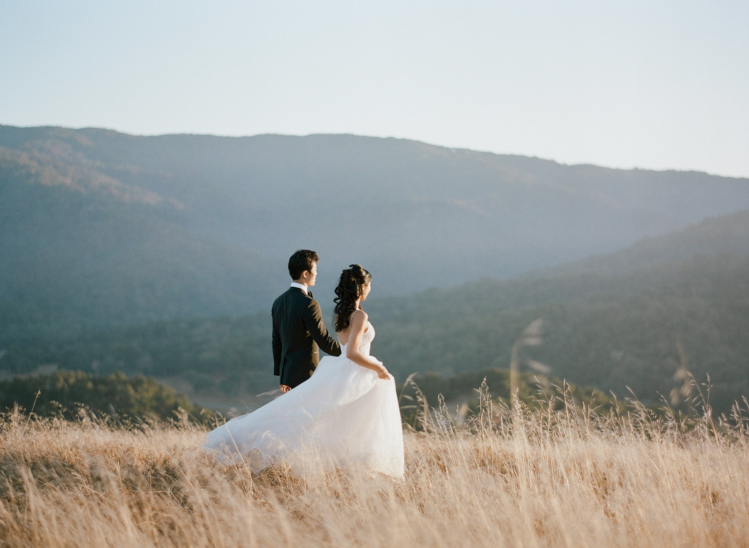 Bride and groom among the grass fields in the hills above Carmel, California at sunset; Sylvie Gil Photography
