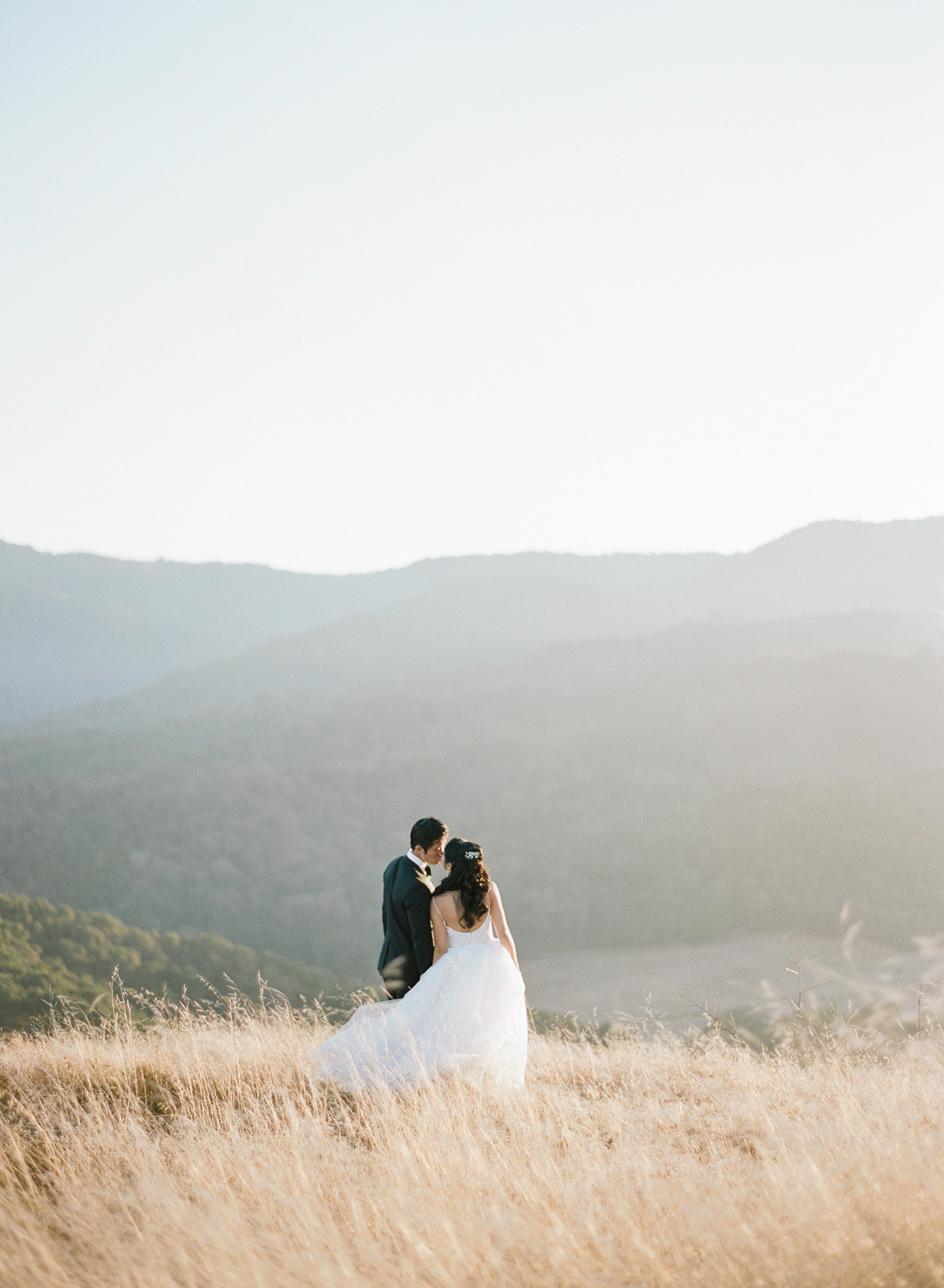 Bride and groom share a kiss at sunset in the Santa Lucia Preserve in Carmel, California; Sylvie Gil Photography
