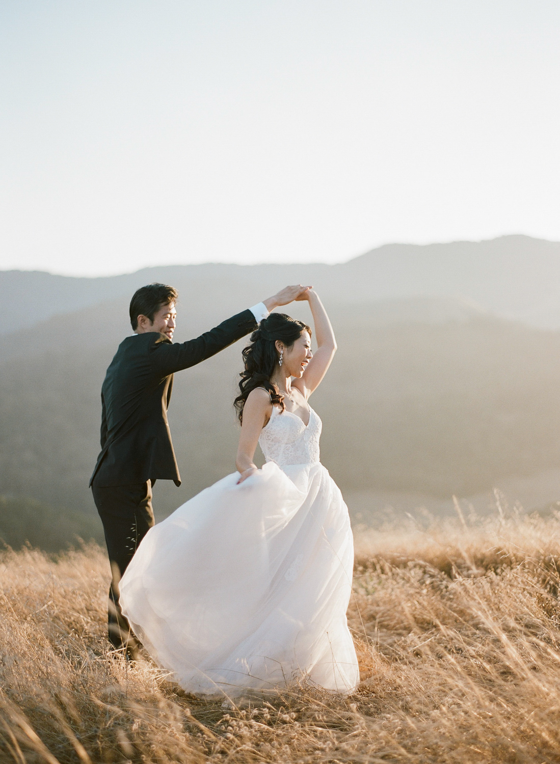 The groom twirls his new wife in a field on the central coast of California at sunset; Sylvie Gil Photography