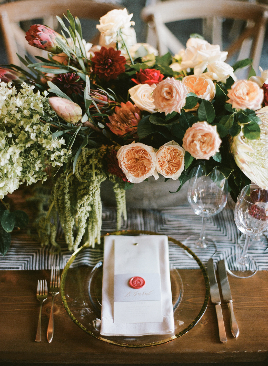 Cream, blush, and crimson peonies decorate a wedding reception table in the Santa Lucia Preserve, in Carmel; Sylvie Gil Photography