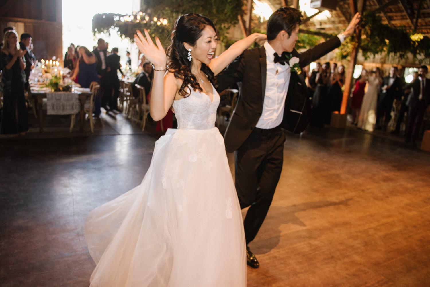 The bride and groom enter the wedding reception for the first time; Sylvie Gil Photography
