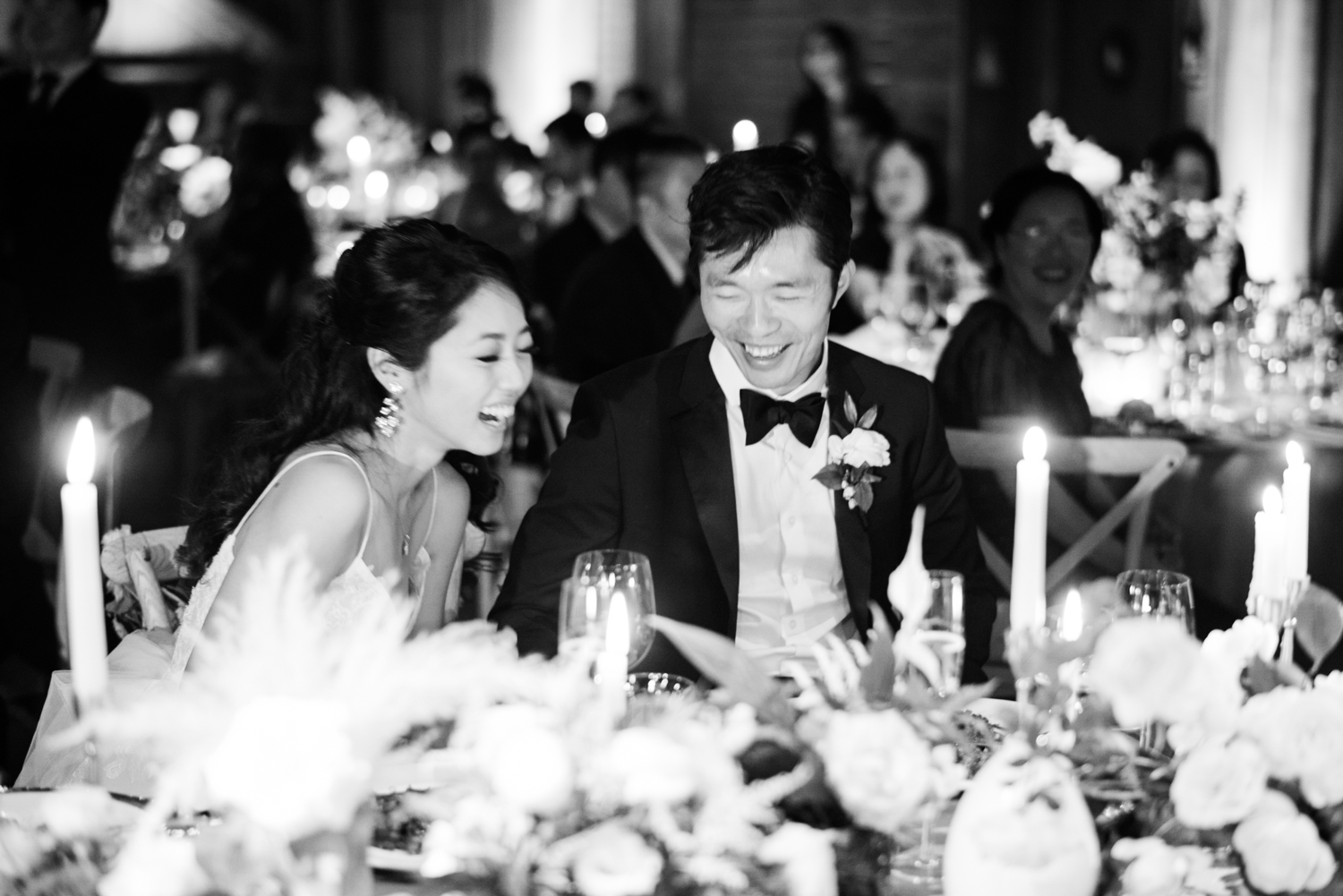 Bride and groom share a laugh during reception toasts at their wedding at the Santa Lucia Preserve in Carmel, California; Sylvie Gil Photography
