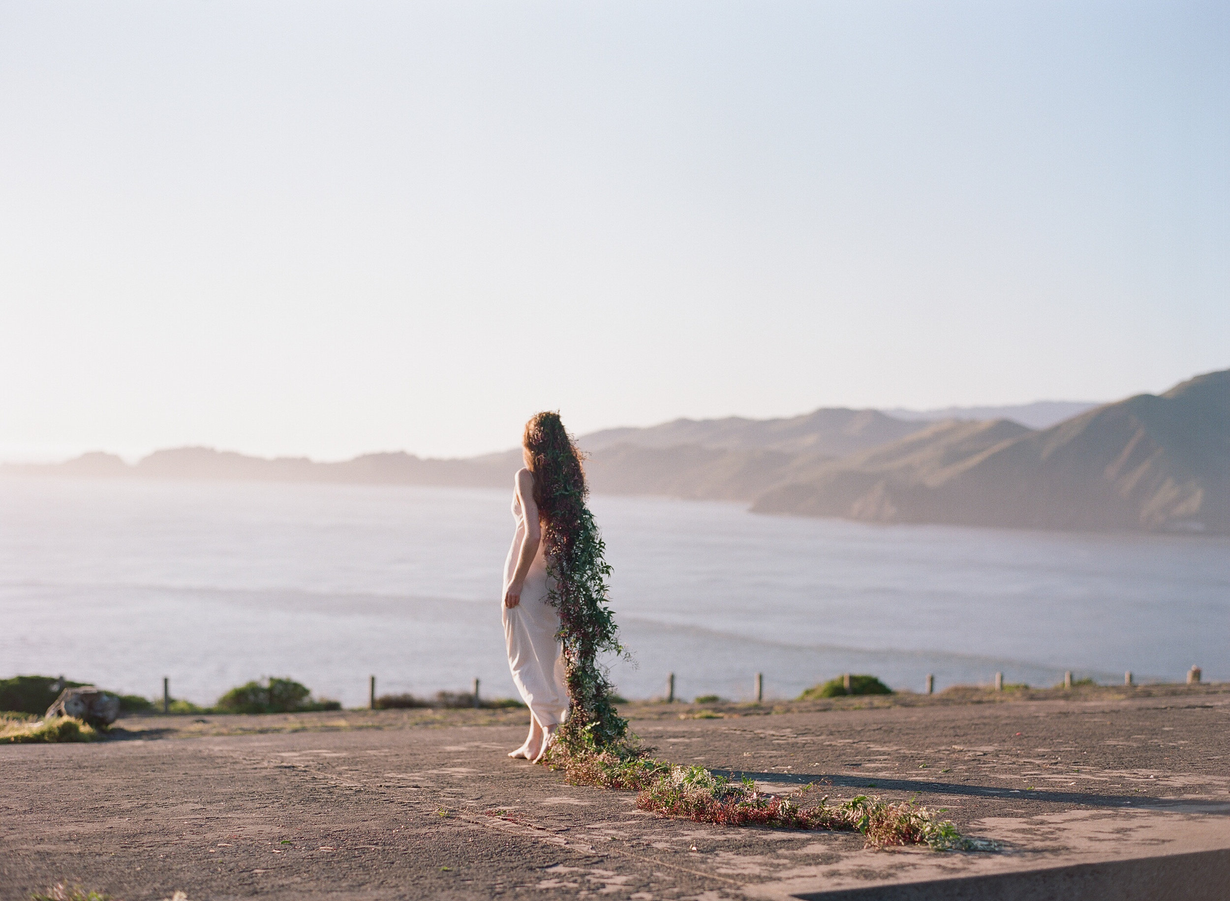 A bride with a long jasmine headpiece looks into a San Francisco sunset; Sylvie Gil Photography