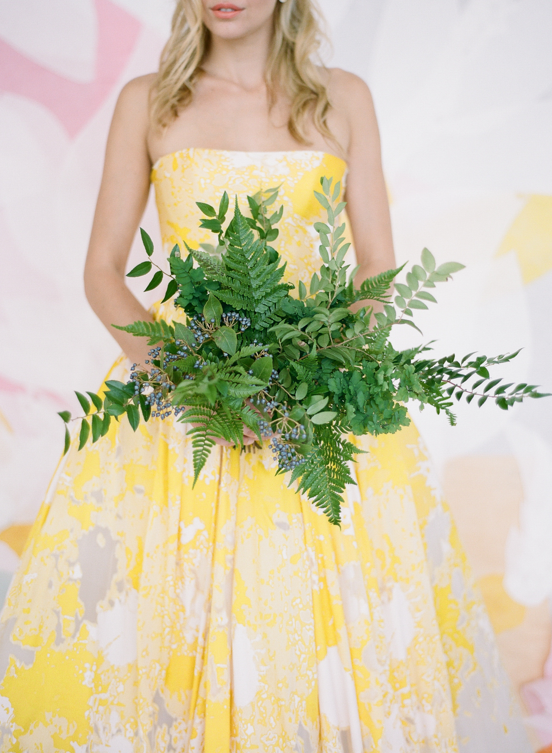 A bride in a yellow and silver strapless gown, with a fern bouquet; Sylvie Gil Photography
