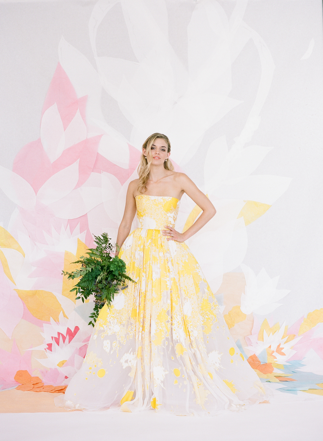 A bride with a fern bouquet in a yellow-painted strapless gown; Sylvie Gil Photography