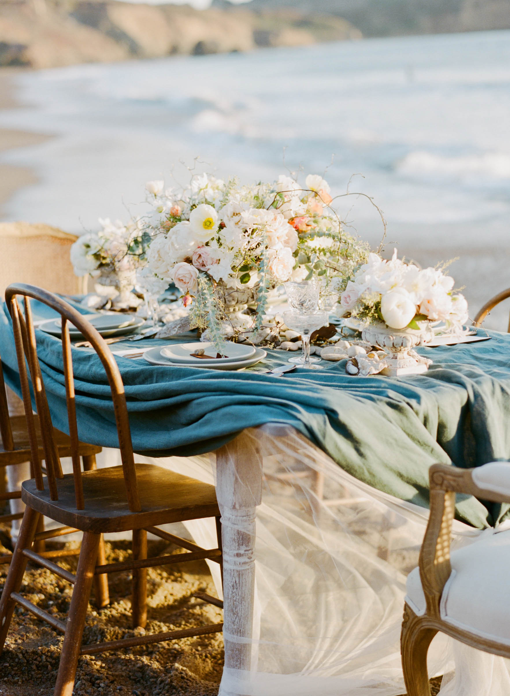 A romantic reception table draped with gauze and deep blue linen on a California beach at sunset; Sylvie Gil Photography