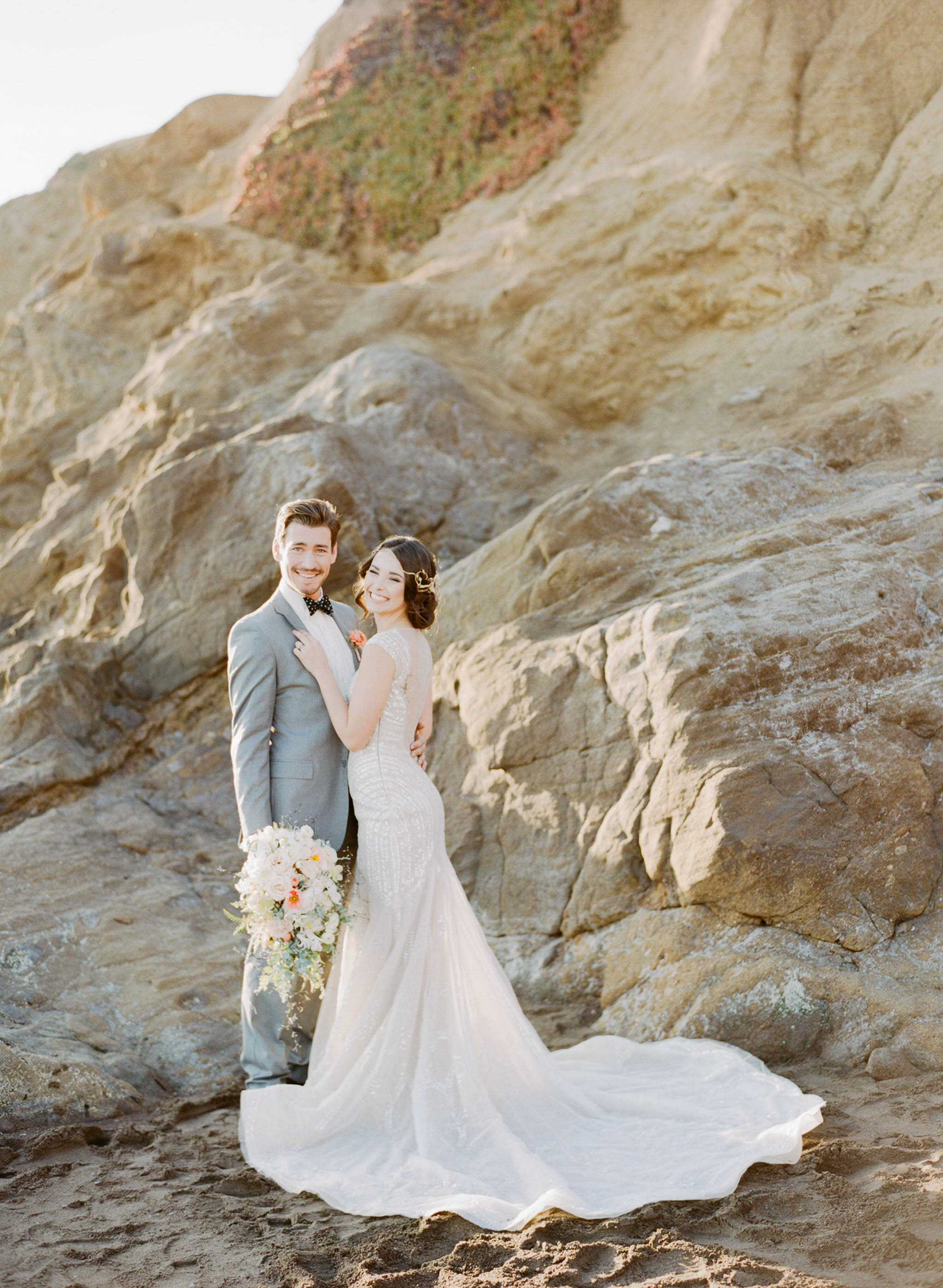 A bride and groom pose by the cliffs on a California beach after their romantic ocean wedding; Sylvie Gil Photography