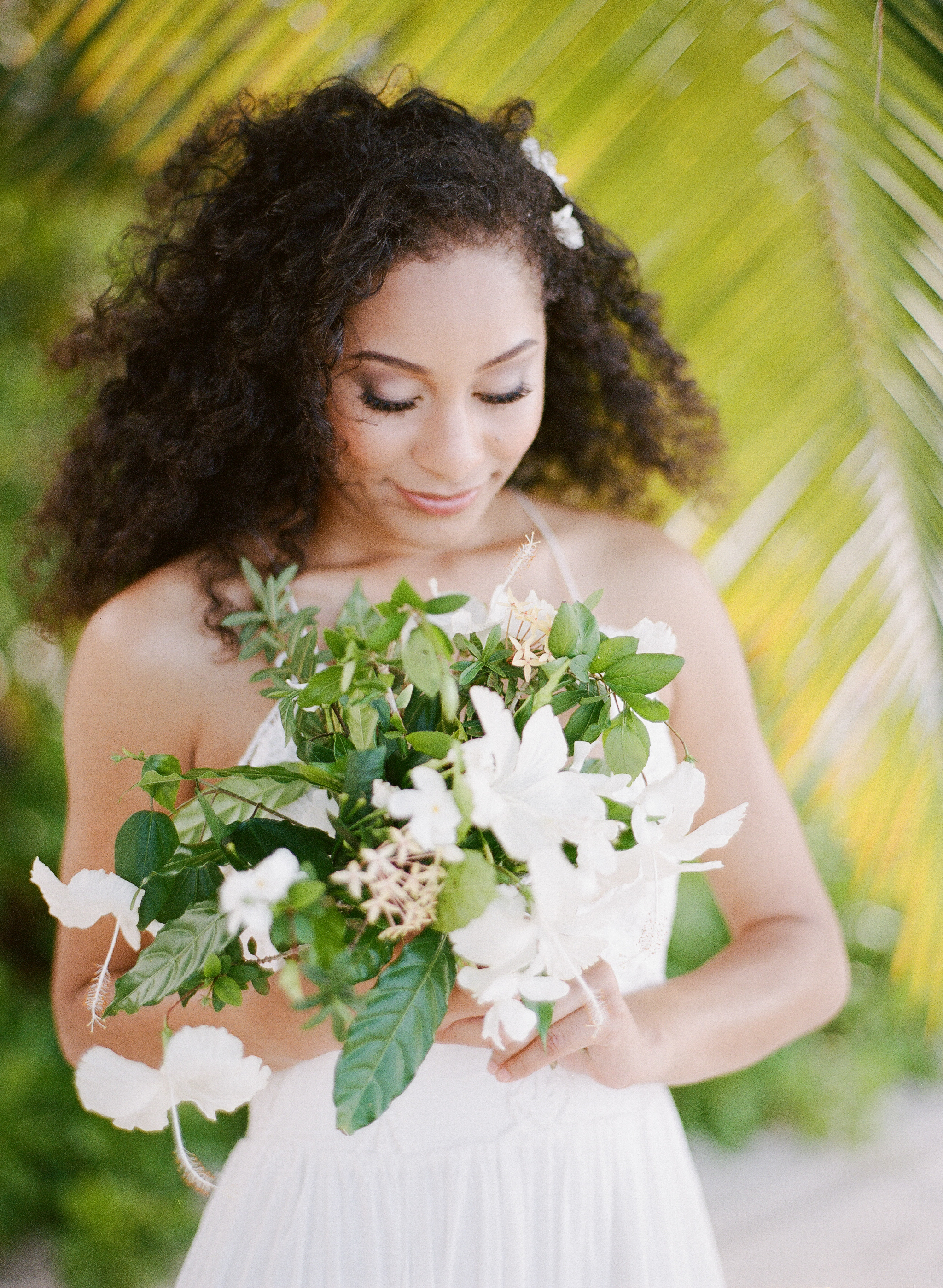A Jamaican bride with a hibiscus bouquet on the beach; Sylvie Gil Photography