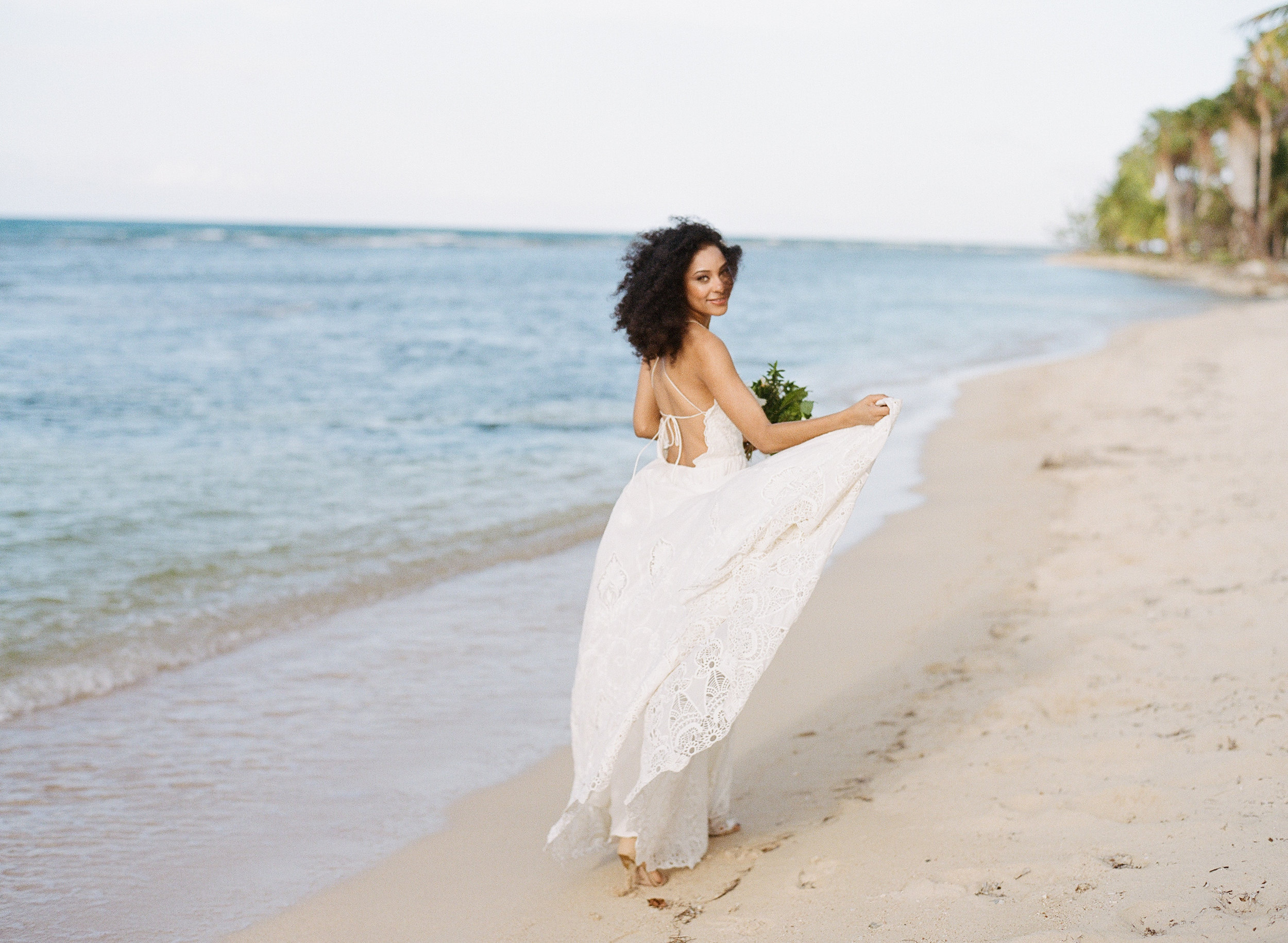 A barefoot Jamaican bride in a flowy backless dress in an editorial shoot on a beach in Montego Bay; Sylvie Gil Photography