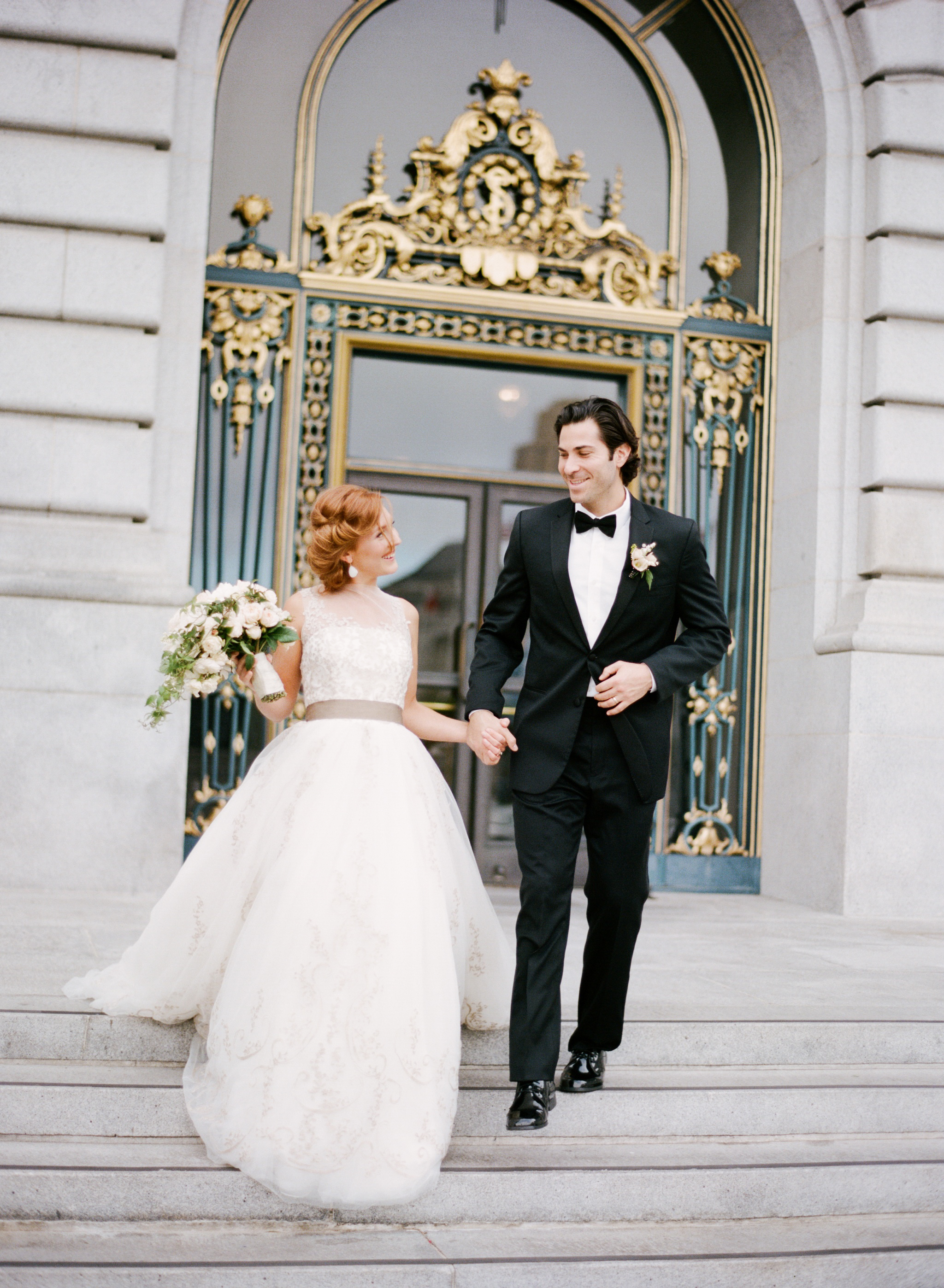 A French couple walks out of San Francisco City Hall just married; Sylvie Gil Photography