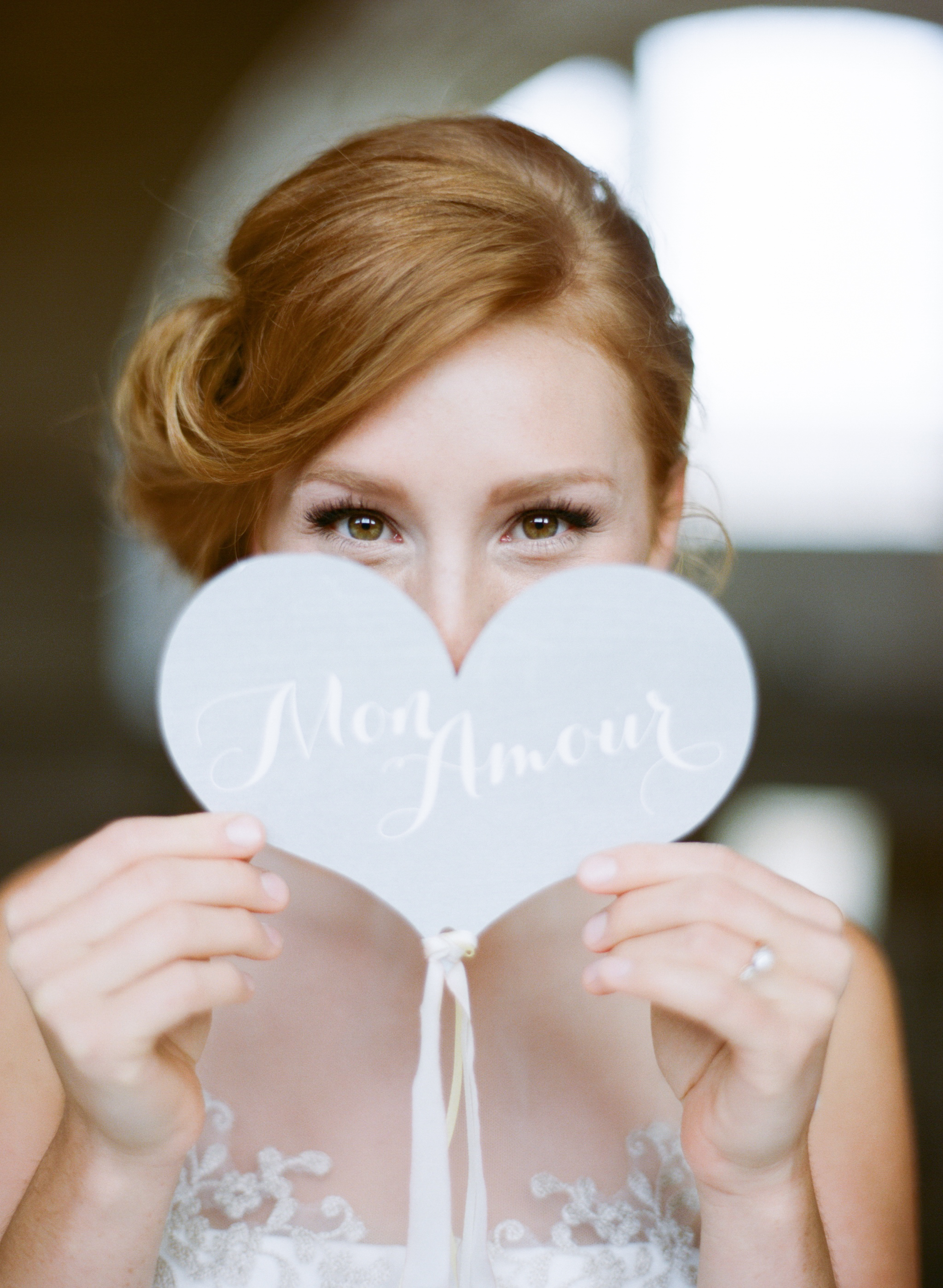 "A redhead bride holds up a sign that says ""Mon amour""; Sylvie Gil Photography"