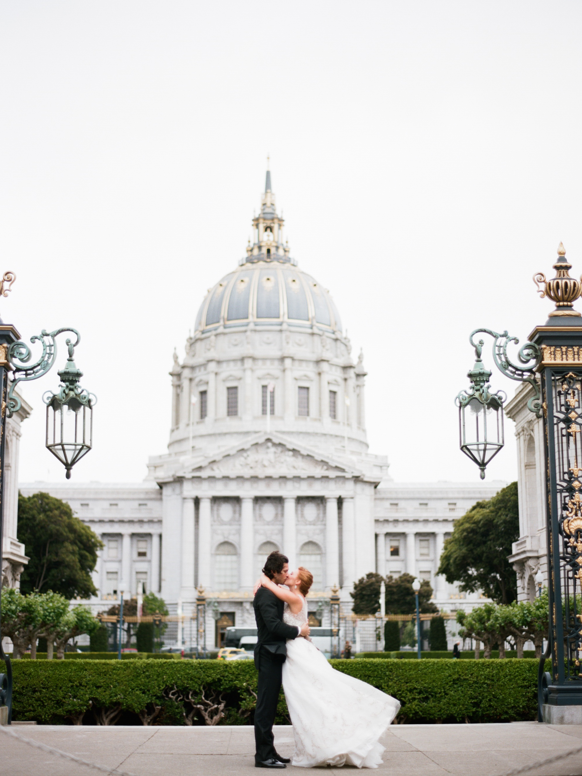 Bride and groom kiss outside San Francisco City Hall, just married; Sylvie Gil Photography