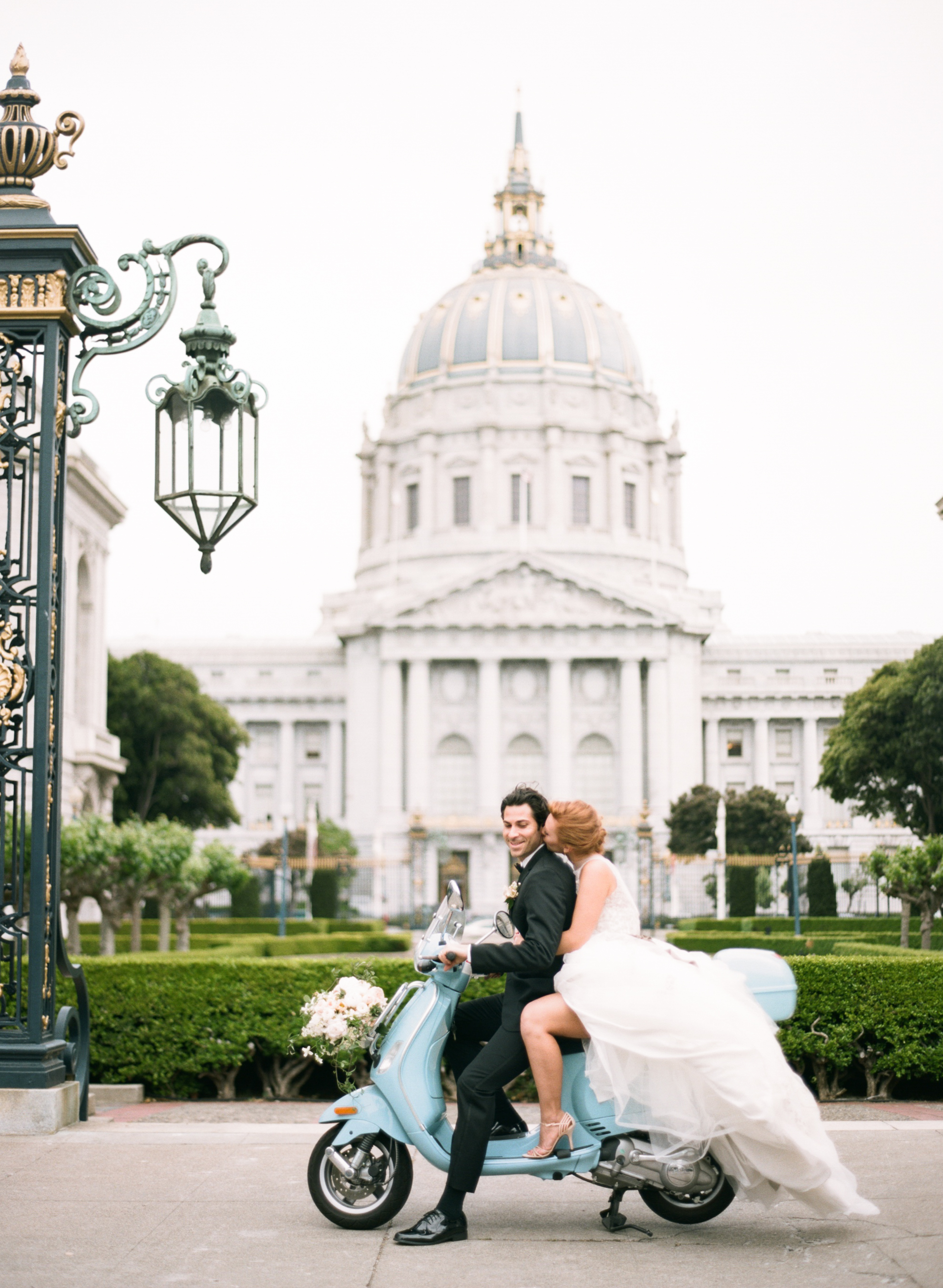 Bride and groom sit on a turquoise Vespa scooter outside San Francisco City Hall; Sylvie Gil Photography