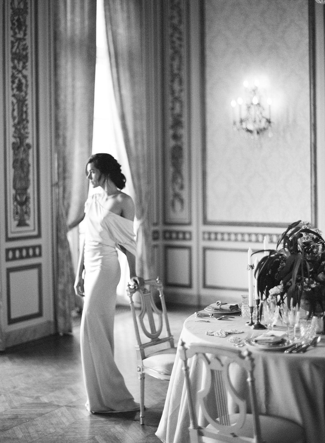 A bride in a one-shoulder gown stands by a reception table in Pavillon de la Musique in Paris, France; Sylvie Gil Photography