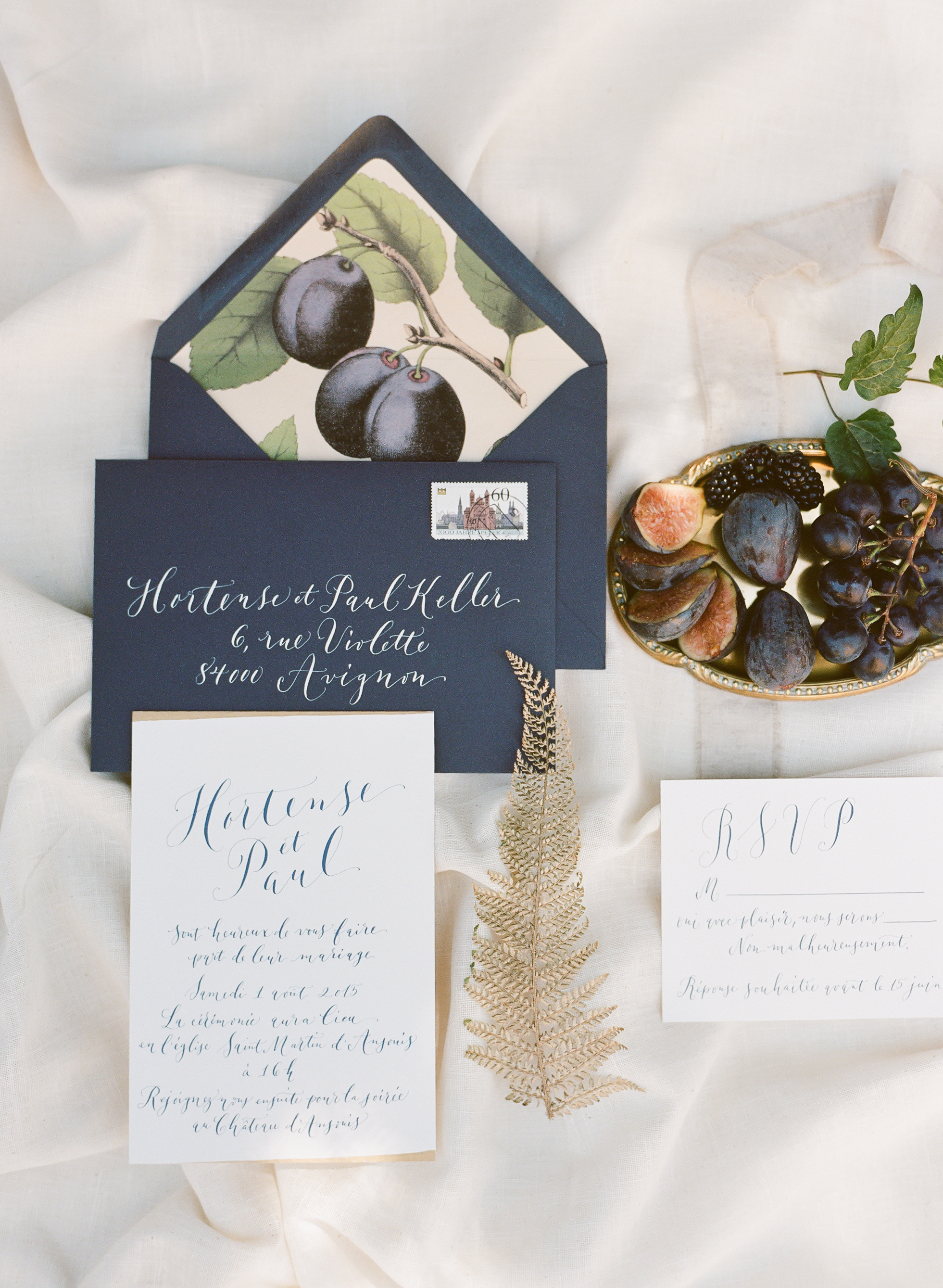 A navy and gold wedding invitation suite decorated with fresh figs; Sylvie Gil Photography