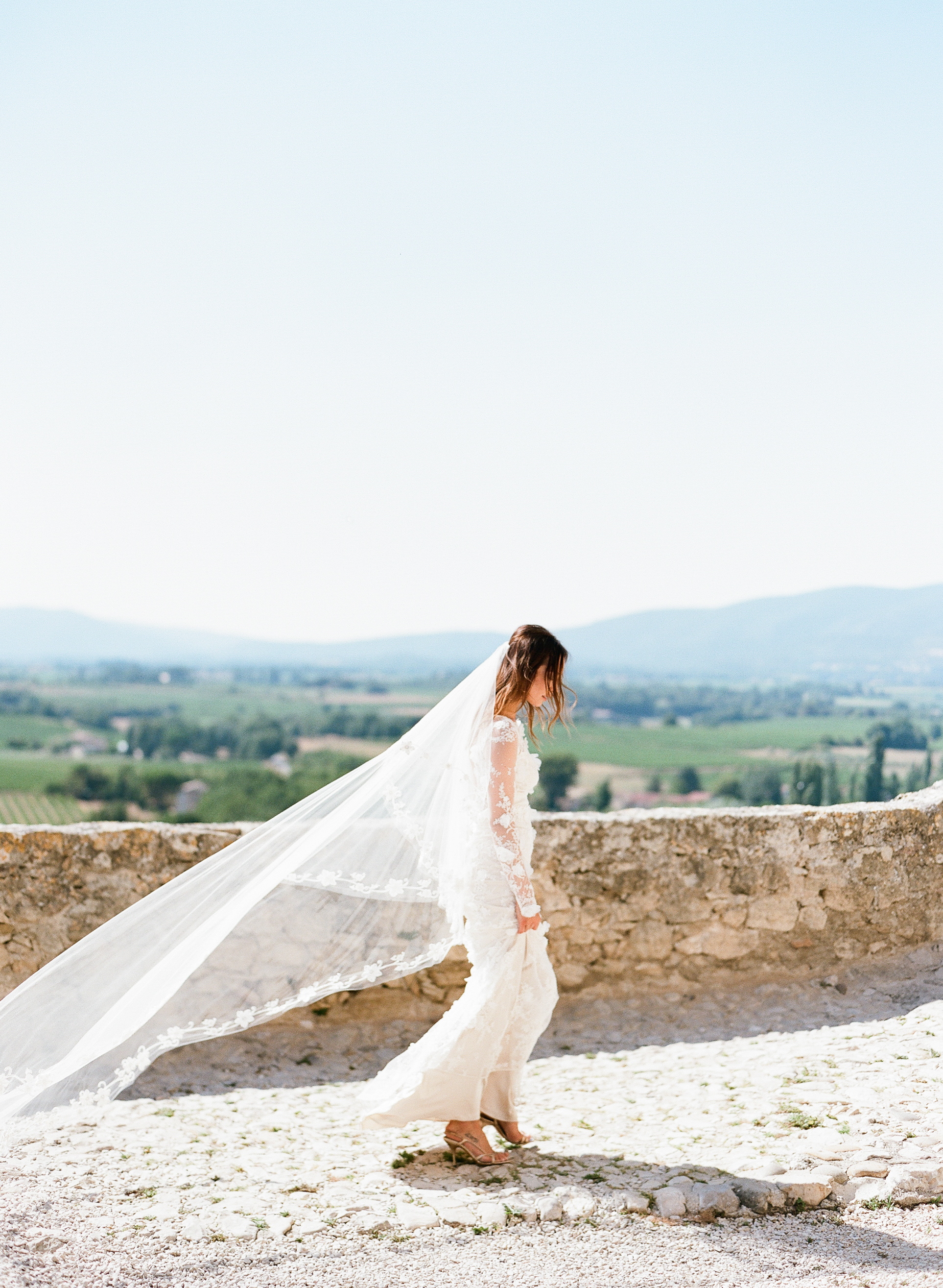 A bride takes a walk on a rooftop in Provence, France; Sylvie Gil Photography