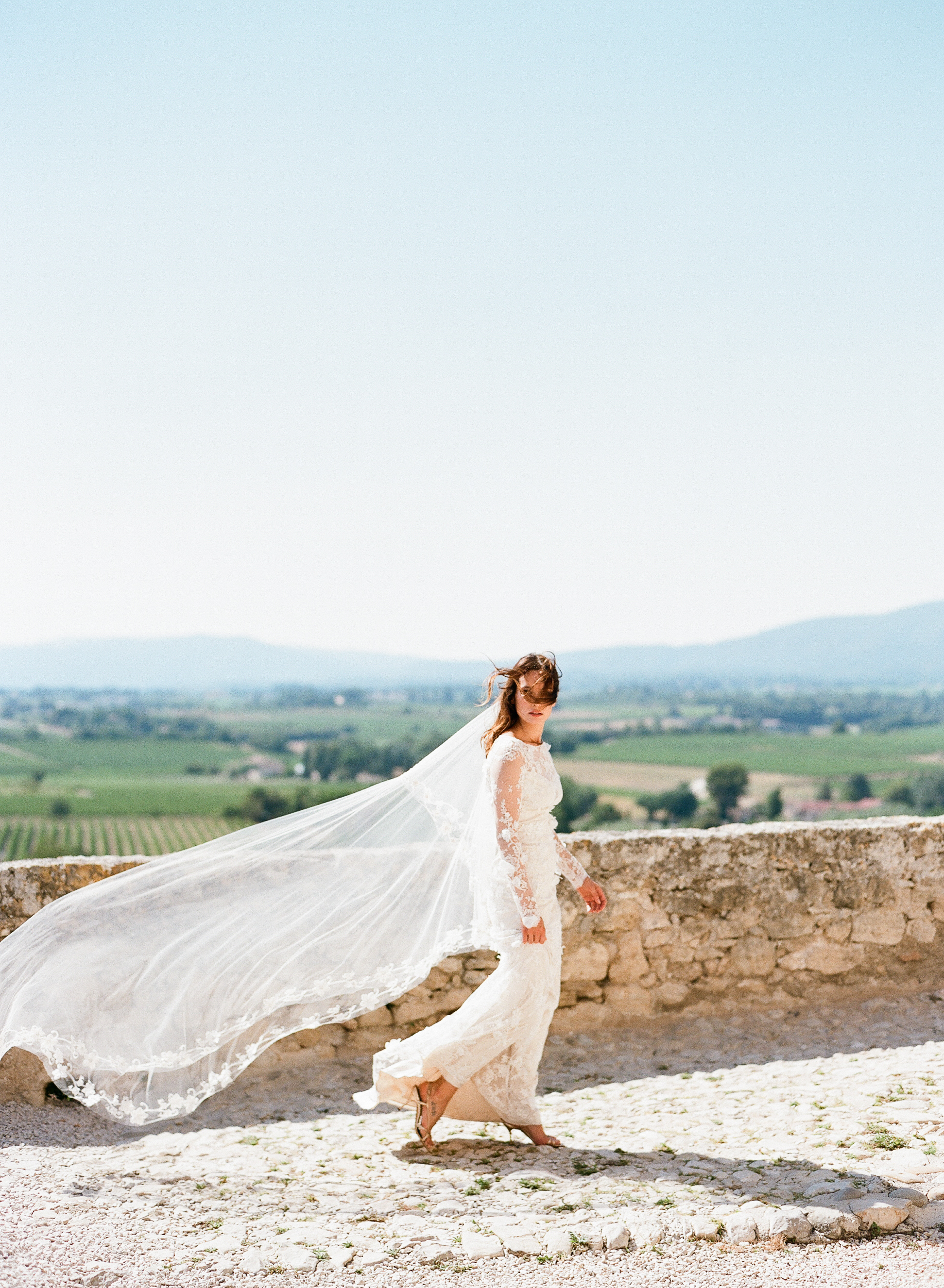 A bride lets her hair blow in the wind on a chateau rooftop in Provence, France; Sylvie Gil Photography