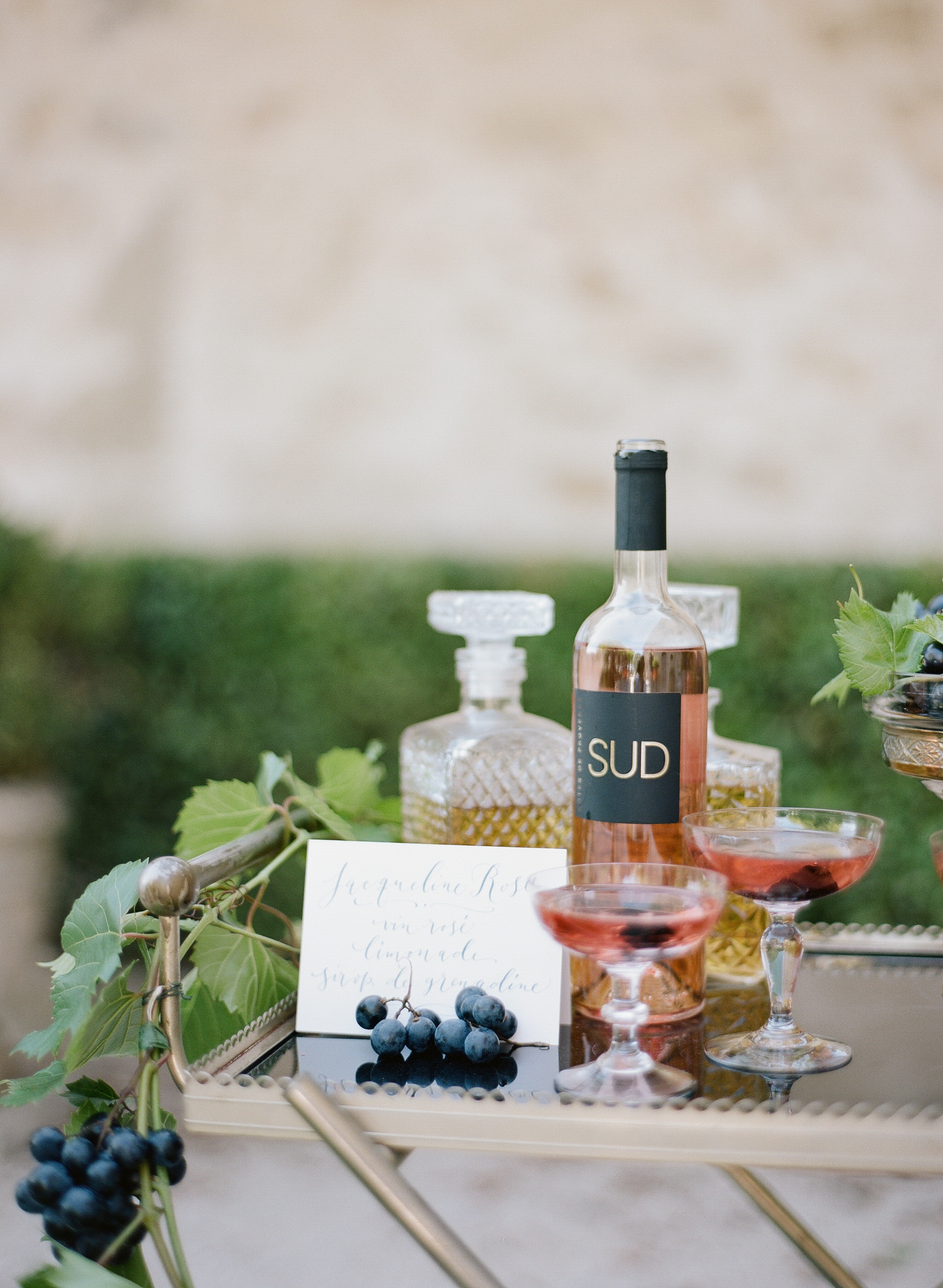 A bar cart with fresh grapes and decanted liquor at an intimate wedding reception in Provence, France; Sylvie Gil Photography