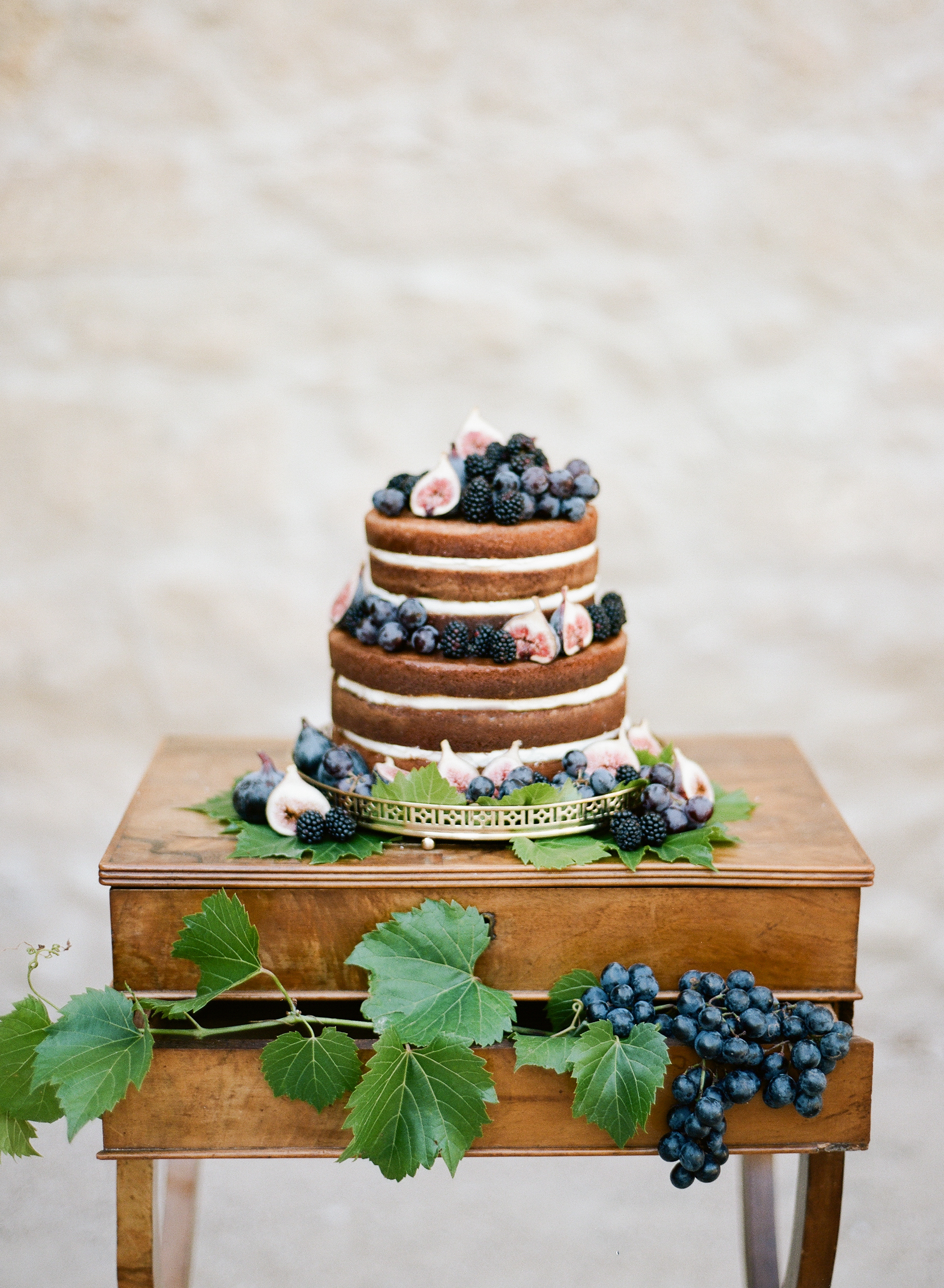 A two-tier naked wedding cake decorated with fresh grapes, blackberries, and figs; Sylvie Gil Photography