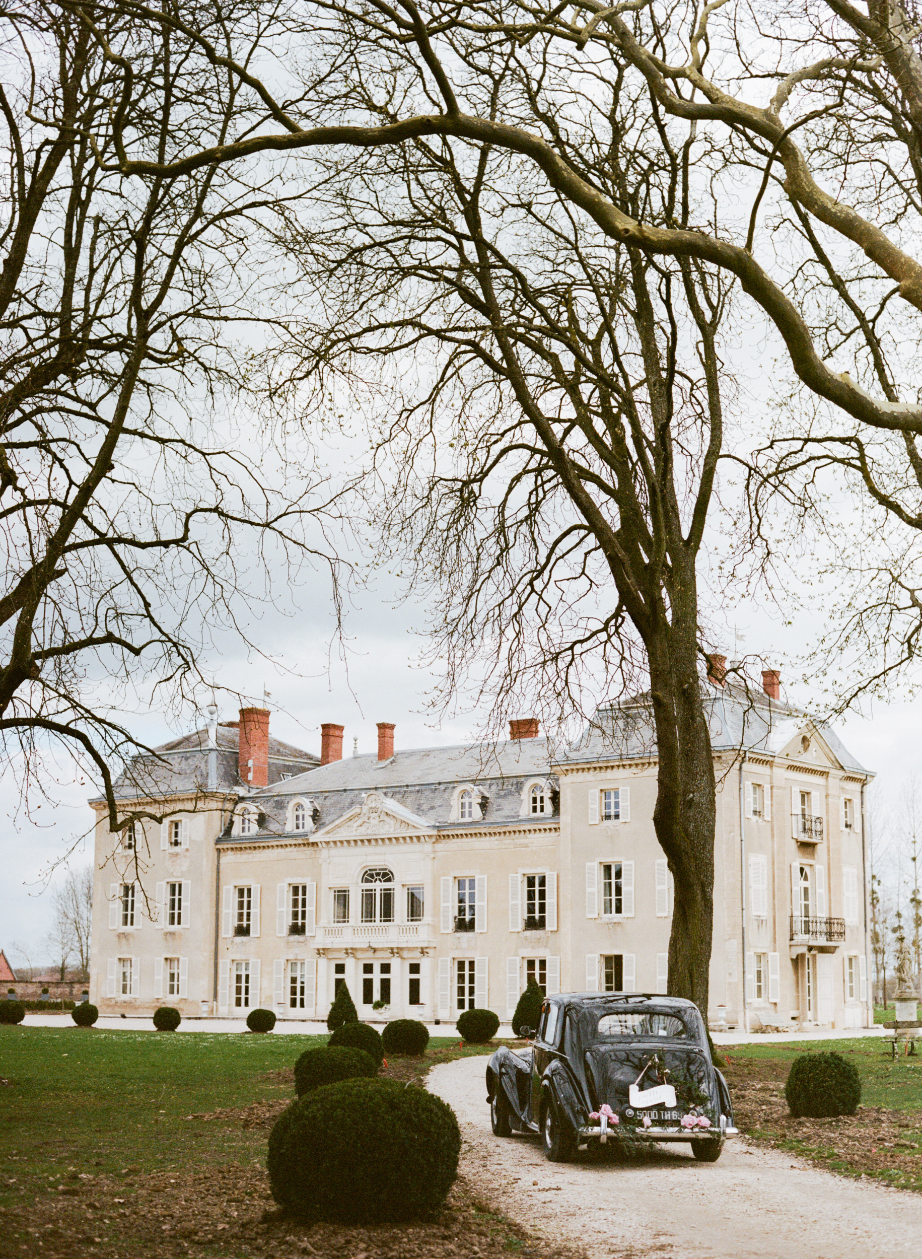 A wedding getaway car parked in front of Chateau de Varennes in Burgundy, France; Sylvie Gil Photography